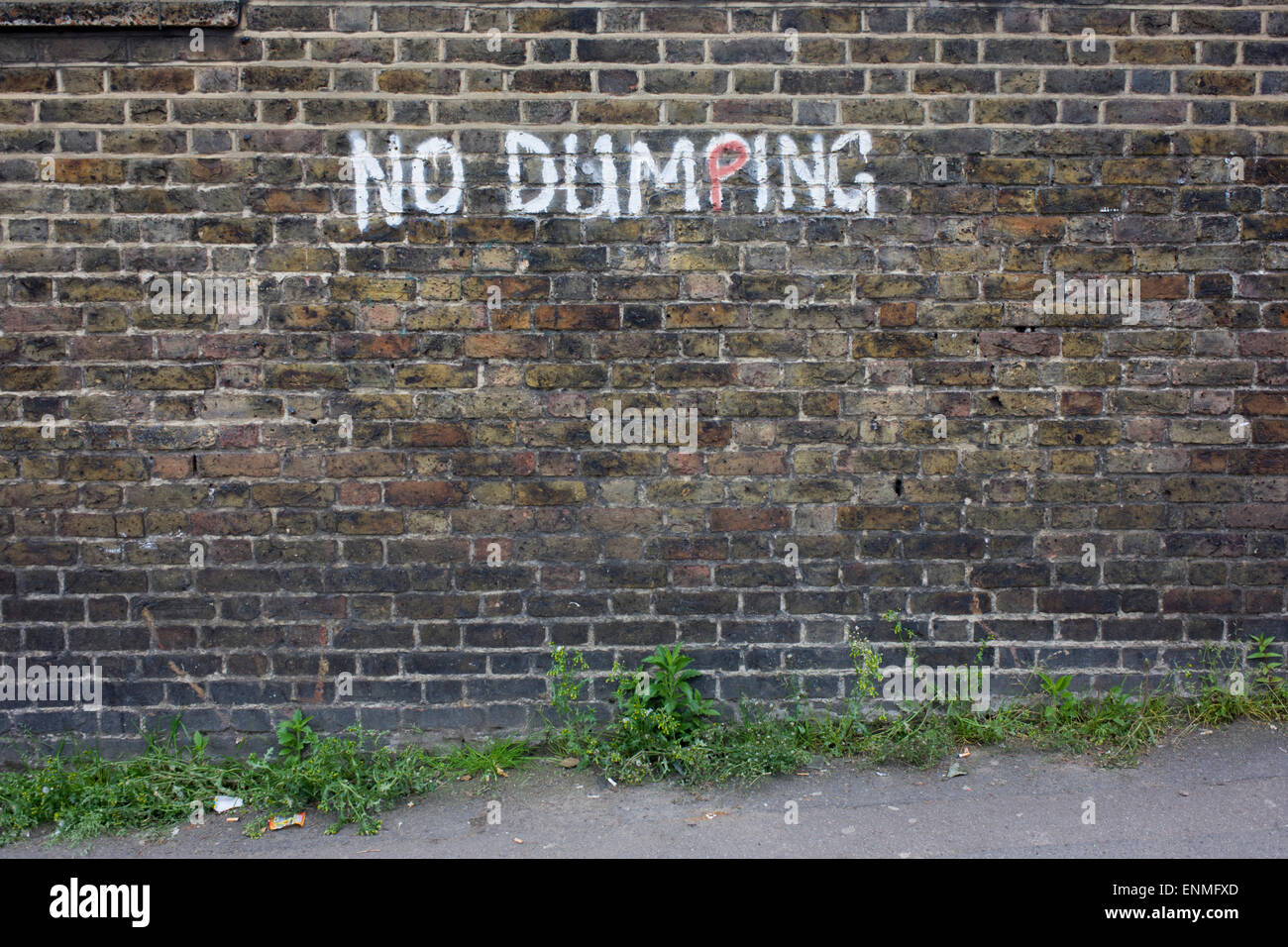 No Dumping writing painted on an urban brick wall in the south London borough of Lewisham, SE5. - Stock Image