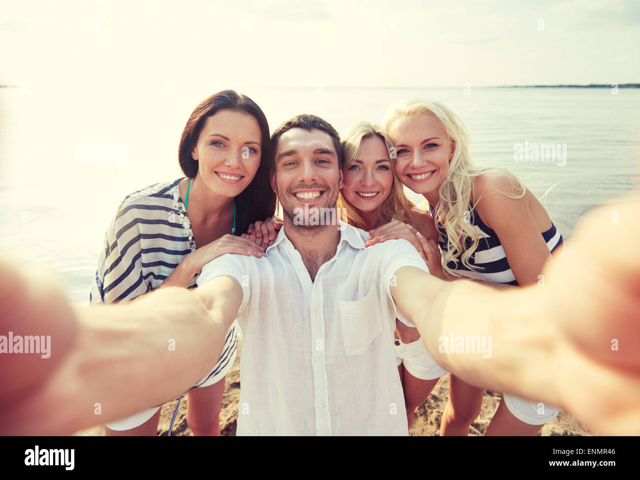 happy friends on beach and taking selfie - Stock Image