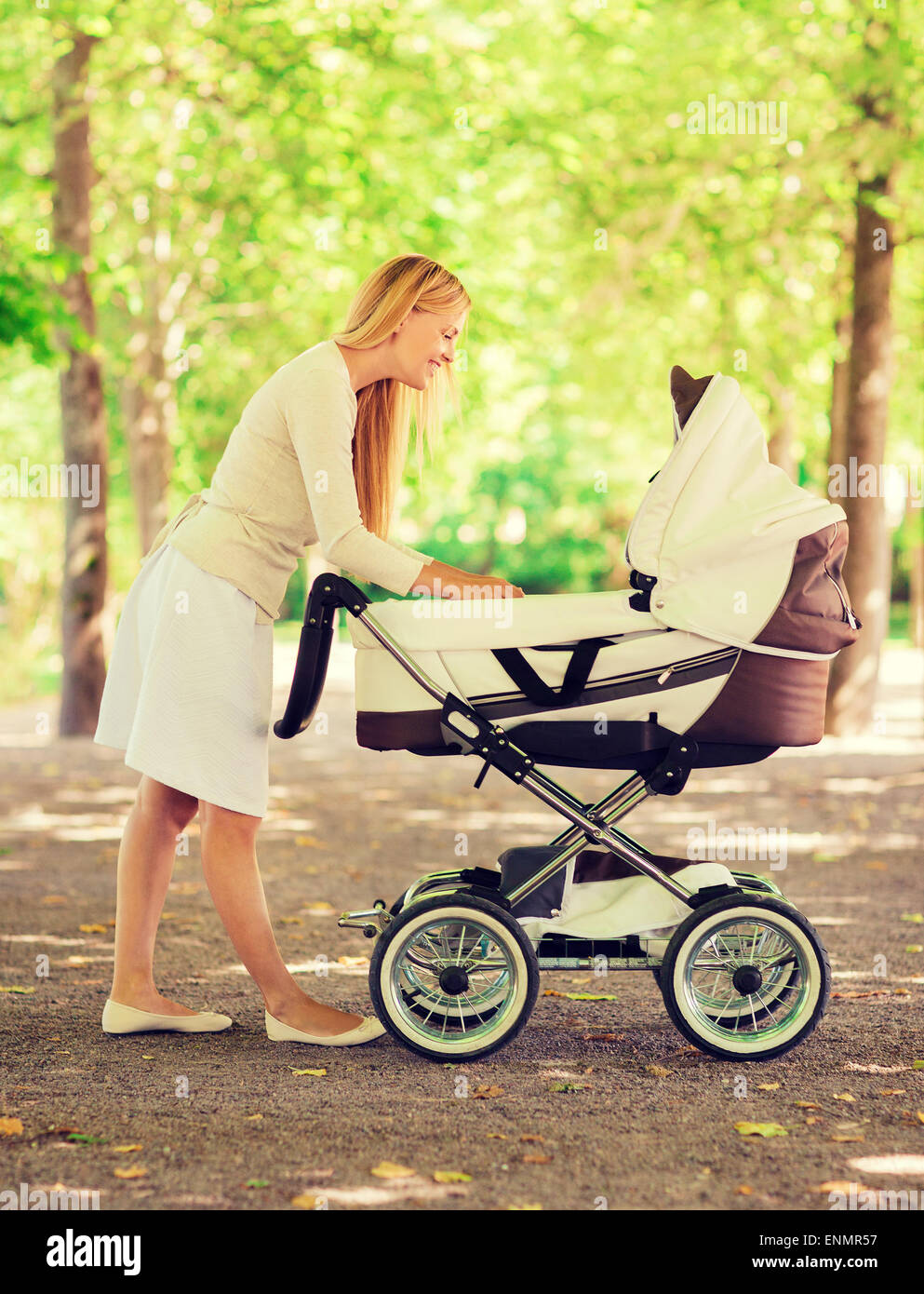 happy mother with stroller in park - Stock Image