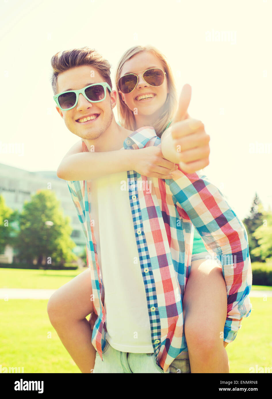 smiling couple having fun and showing thumbs up - Stock Image