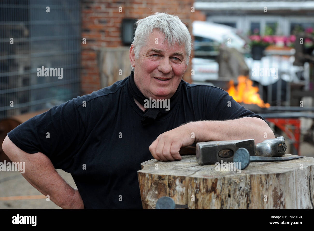 """Friesoythe, Germany. 8th May, 2015. Actor Heinz Hoenig works on a nail at the """"Bullermanns Schmiedeatelier"""" (lit. Stock Photo"""