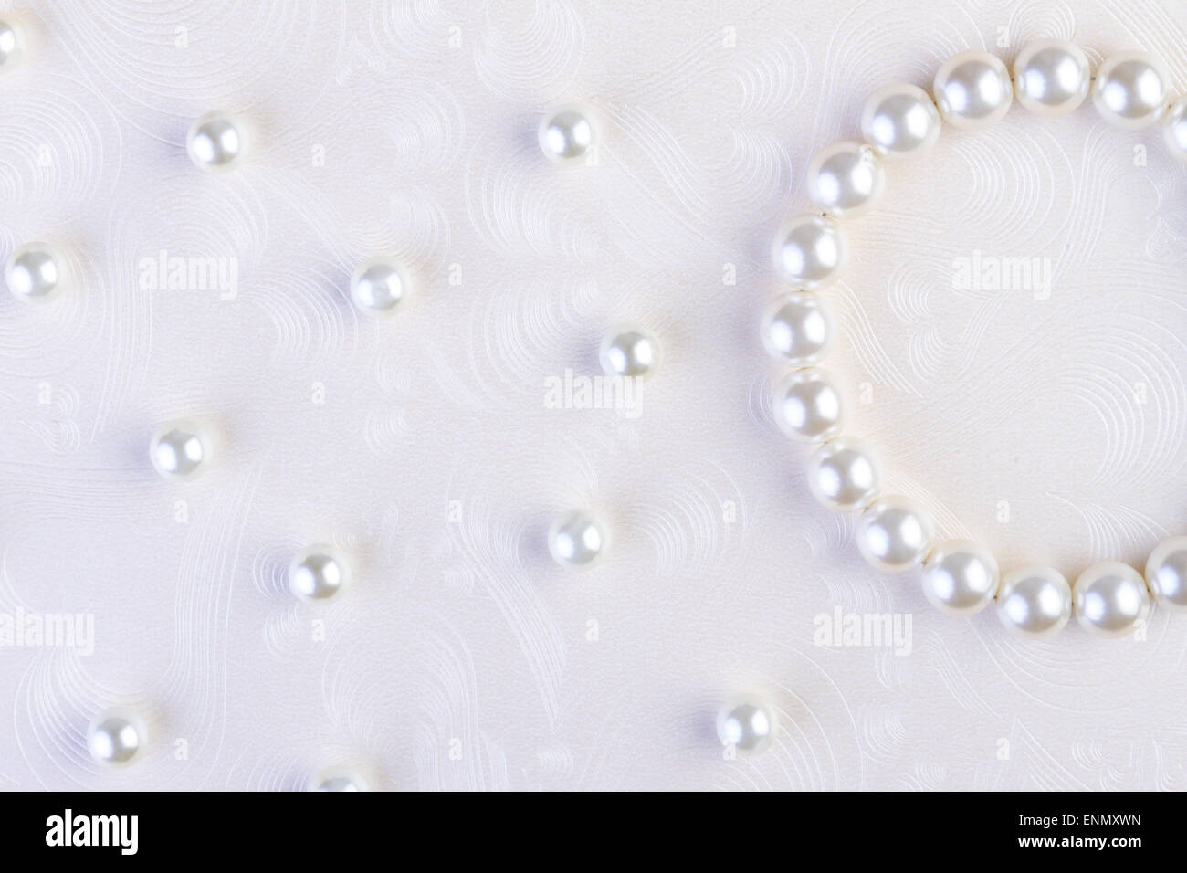 White pearls necklace on white paper background - Stock Image