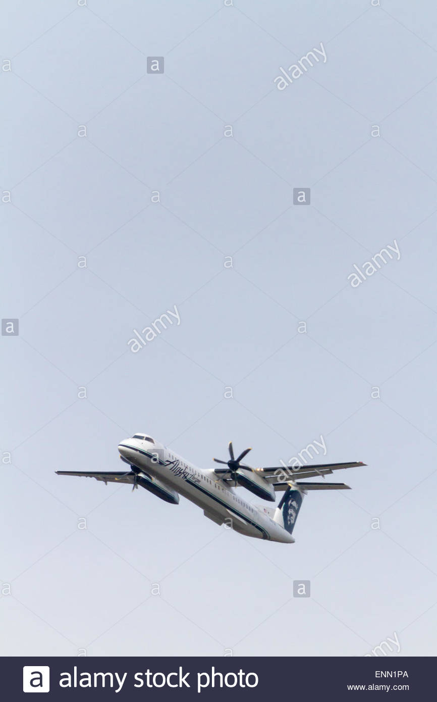 An Alaska Airline Horizon Bombardier Q400 turbo prop airplanes takes off with flaps extended - Stock Image