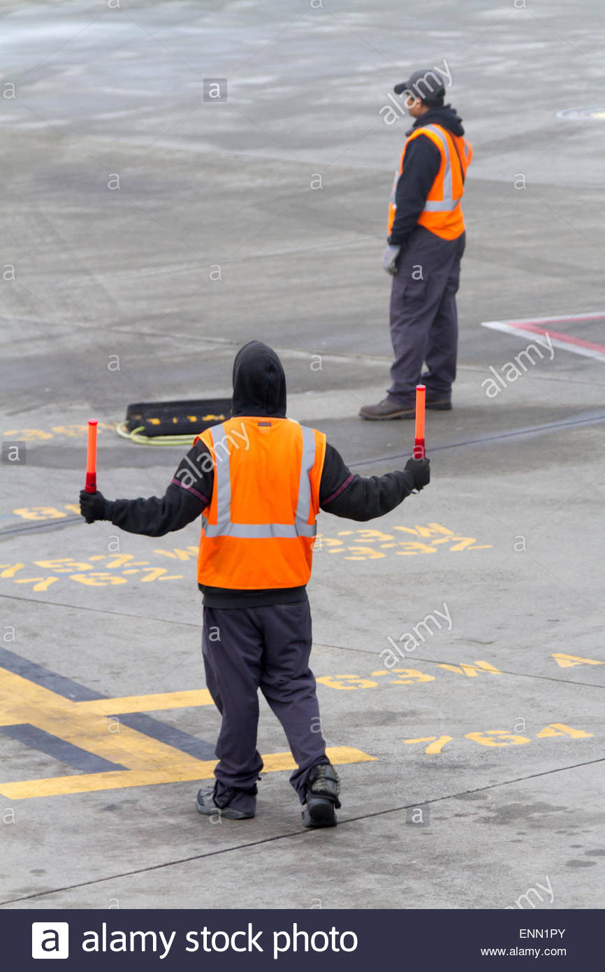 An airport work directs an incoming airplane to its parking location while another worker holds wheel chocks. - Stock Image