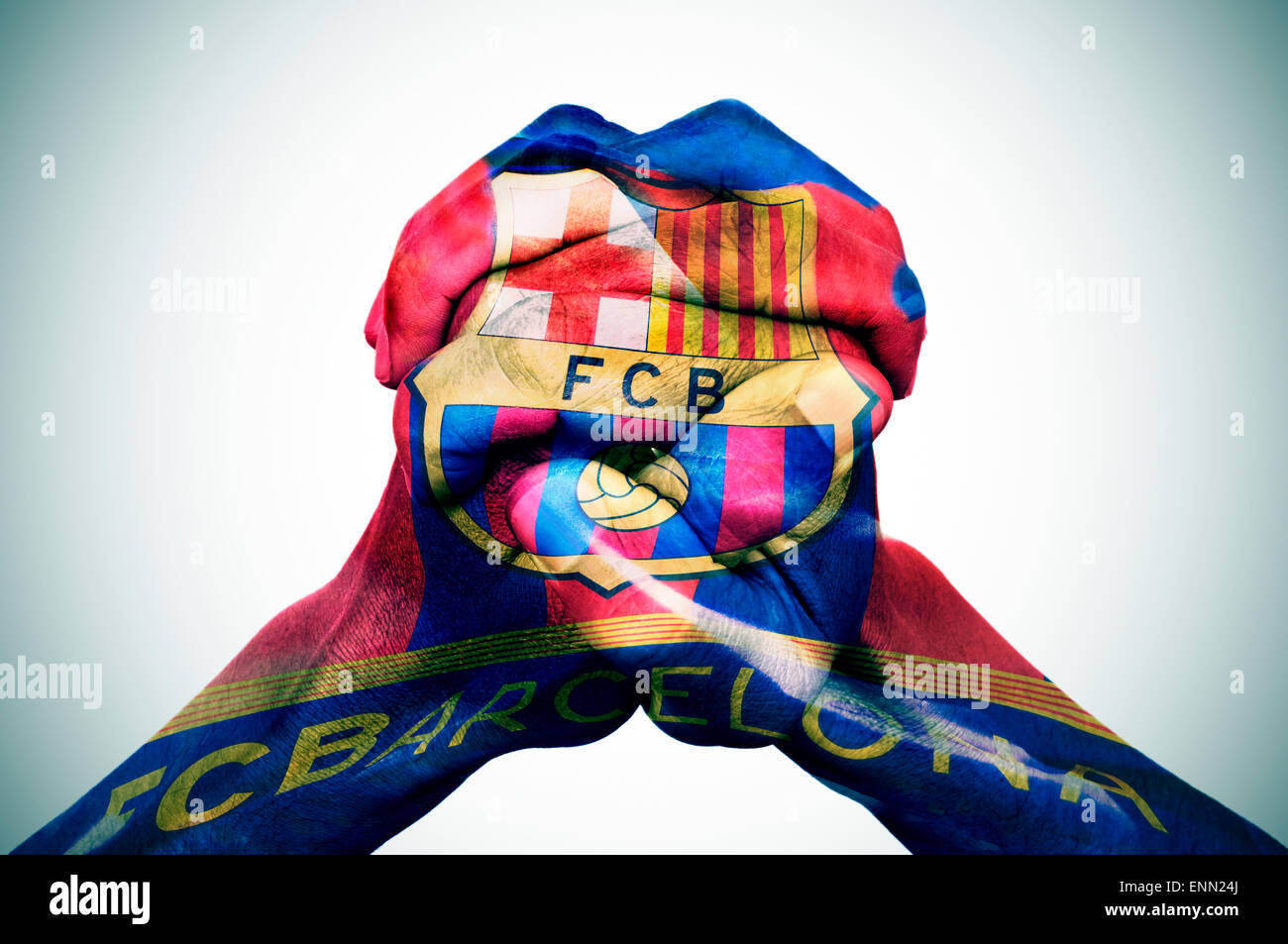 the clasped hands of a young man patterned with the flag of the Futbol Club Barcelona, also known as Barca - Stock Image