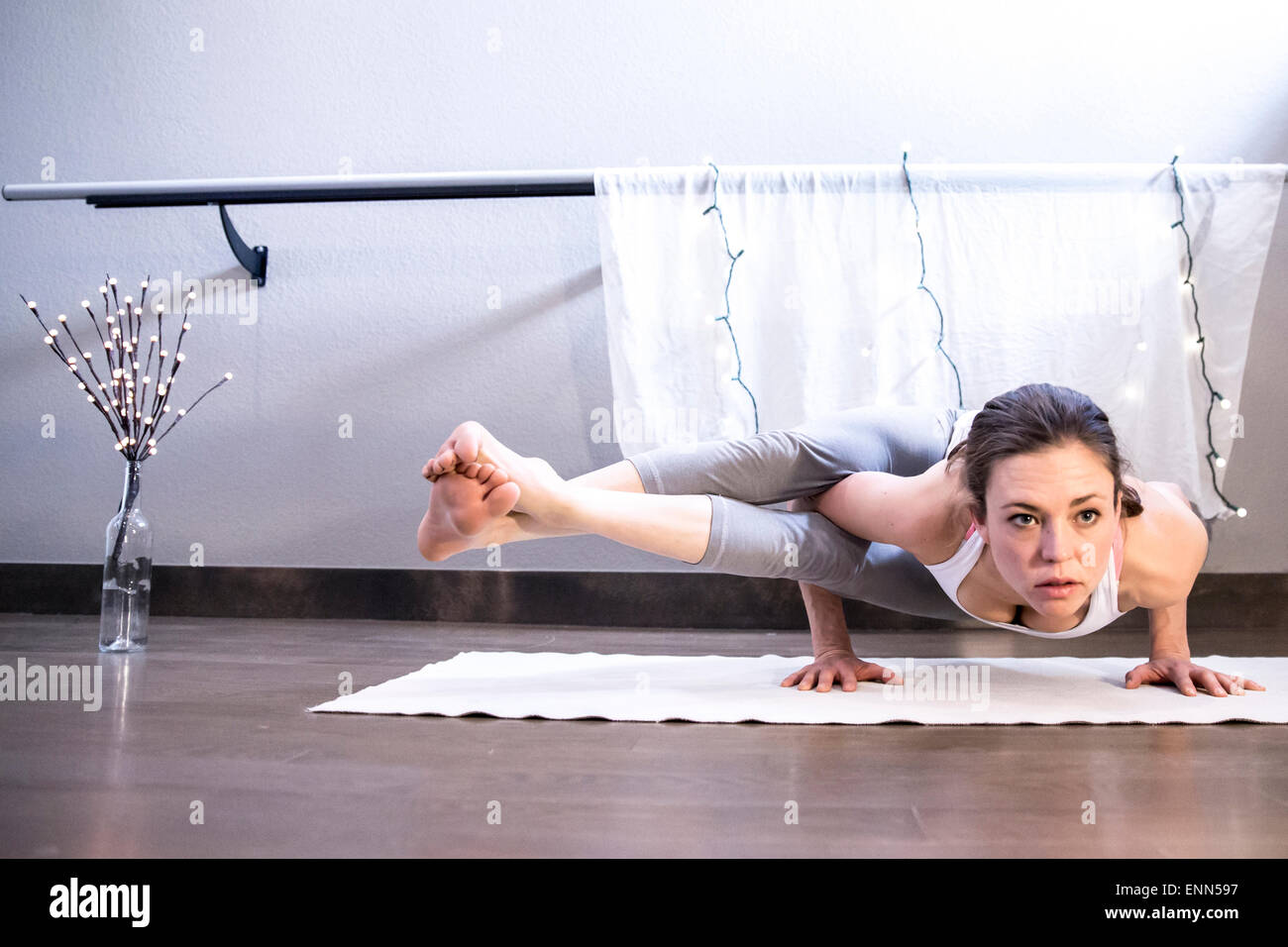 Strong Female holds yoga arm balance - Stock Image