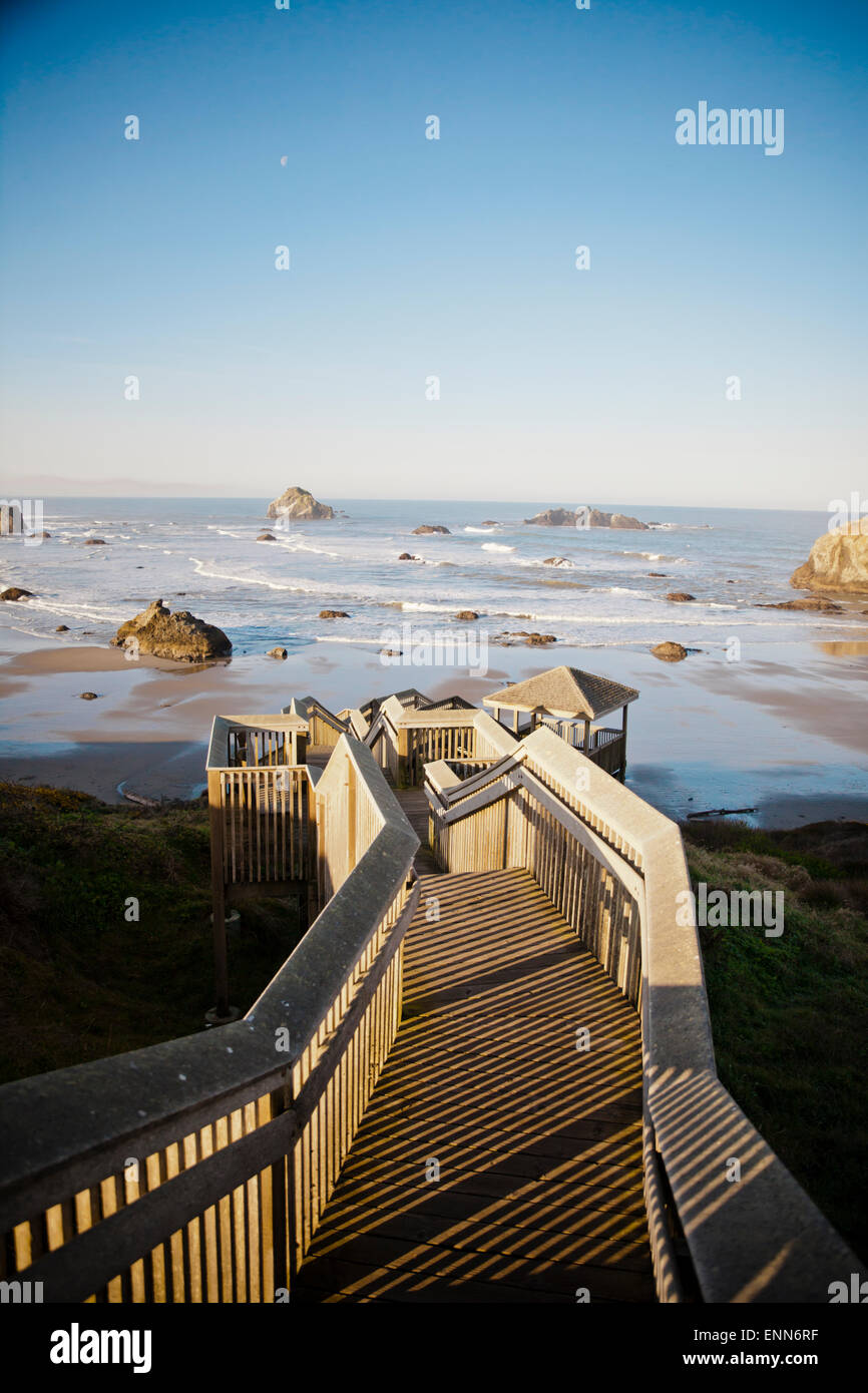 The morning sun shines on a long wooden staircase that leads down to Bandon Bay on the Oregon Coast. - Stock Image
