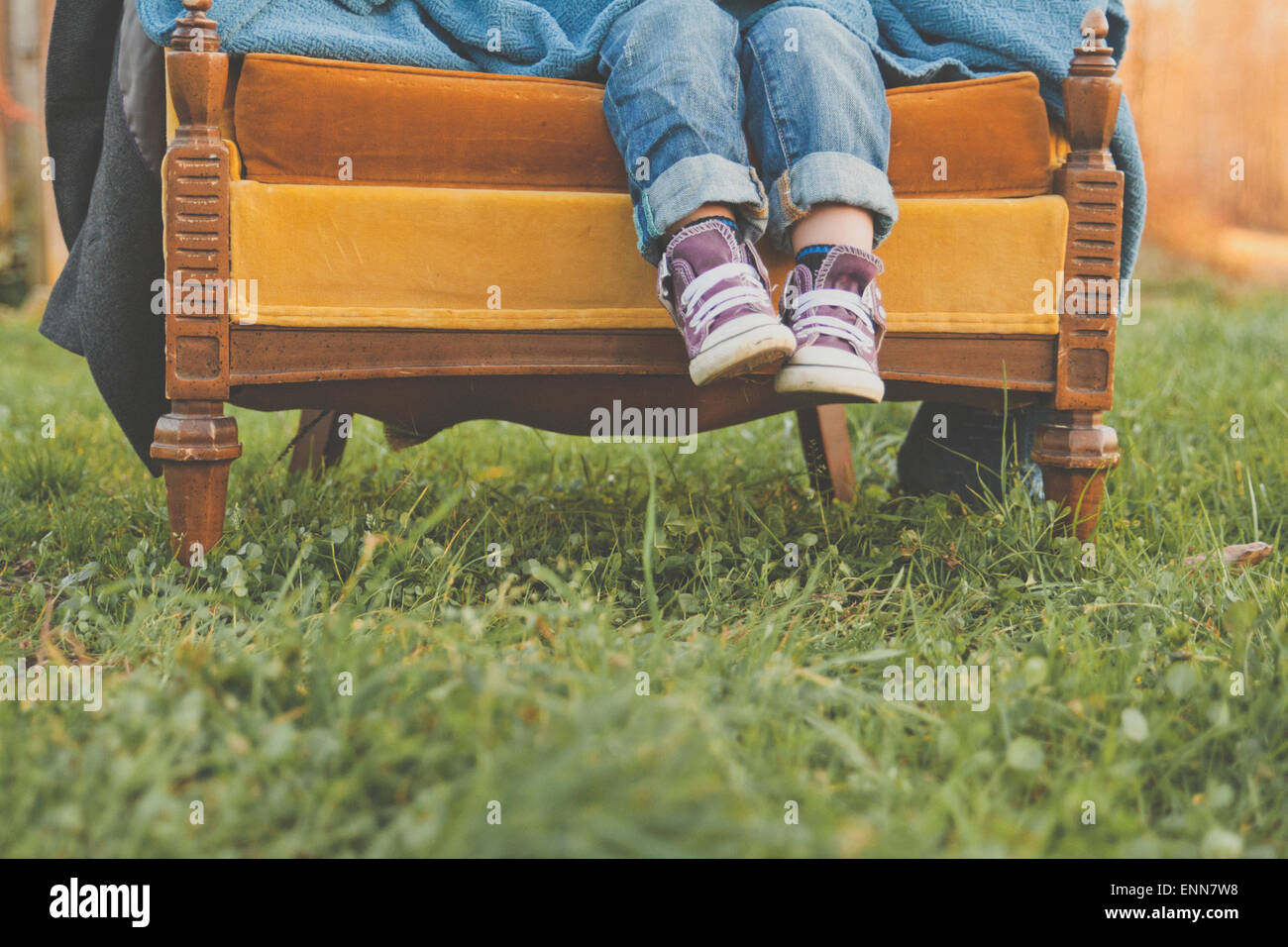 A young boys feet dangle off the end of an old chair in a grassy field. - Stock Image