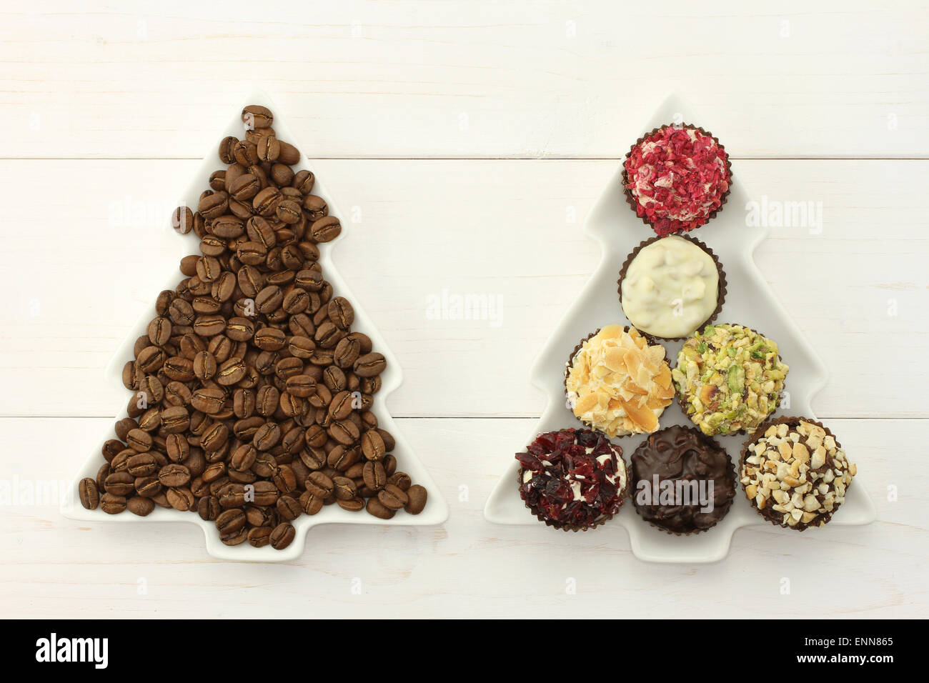 Two dish-spruces with roasted coffee beans  and set of chocolates on the white wooden background - Stock Image