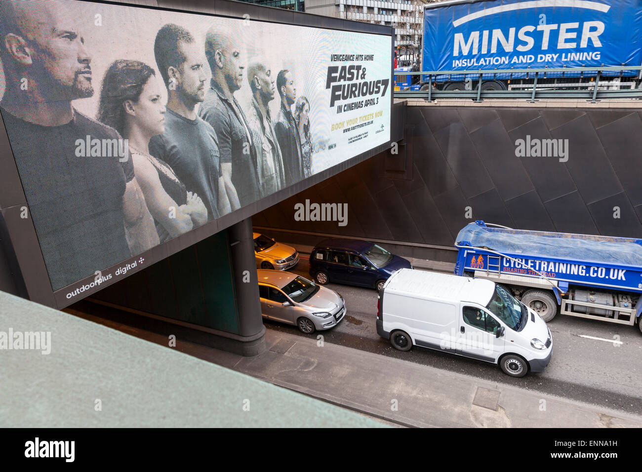 Irony. Fast and furious advertising above vehicles at a standstill. City traffic jam, London, England, UK - Stock Image
