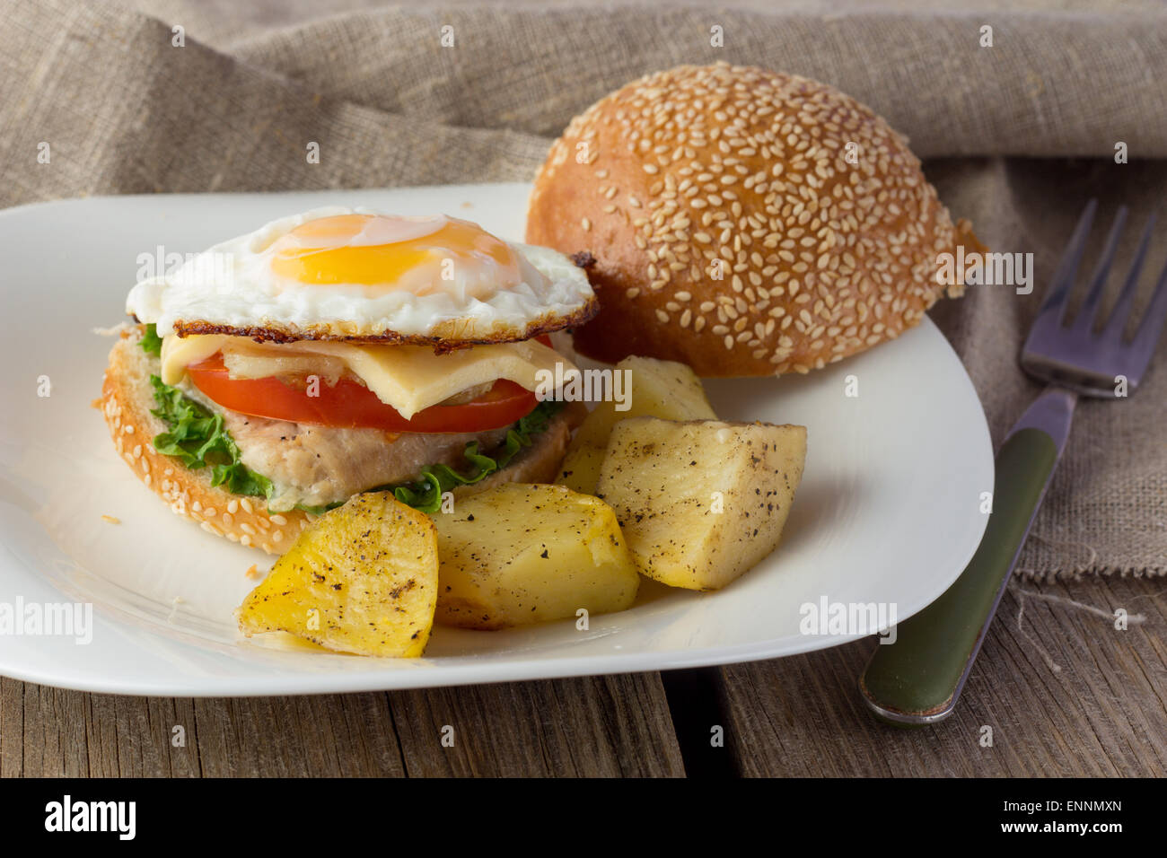 Cheeseburger with fried egg and potato vedges horizontal selective focus Stock Photo