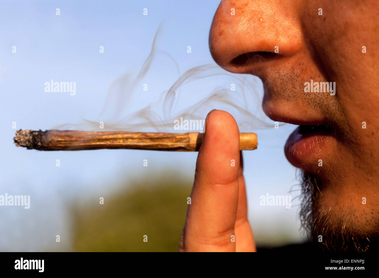 Close up, man smoking marijuana joint - Stock Image