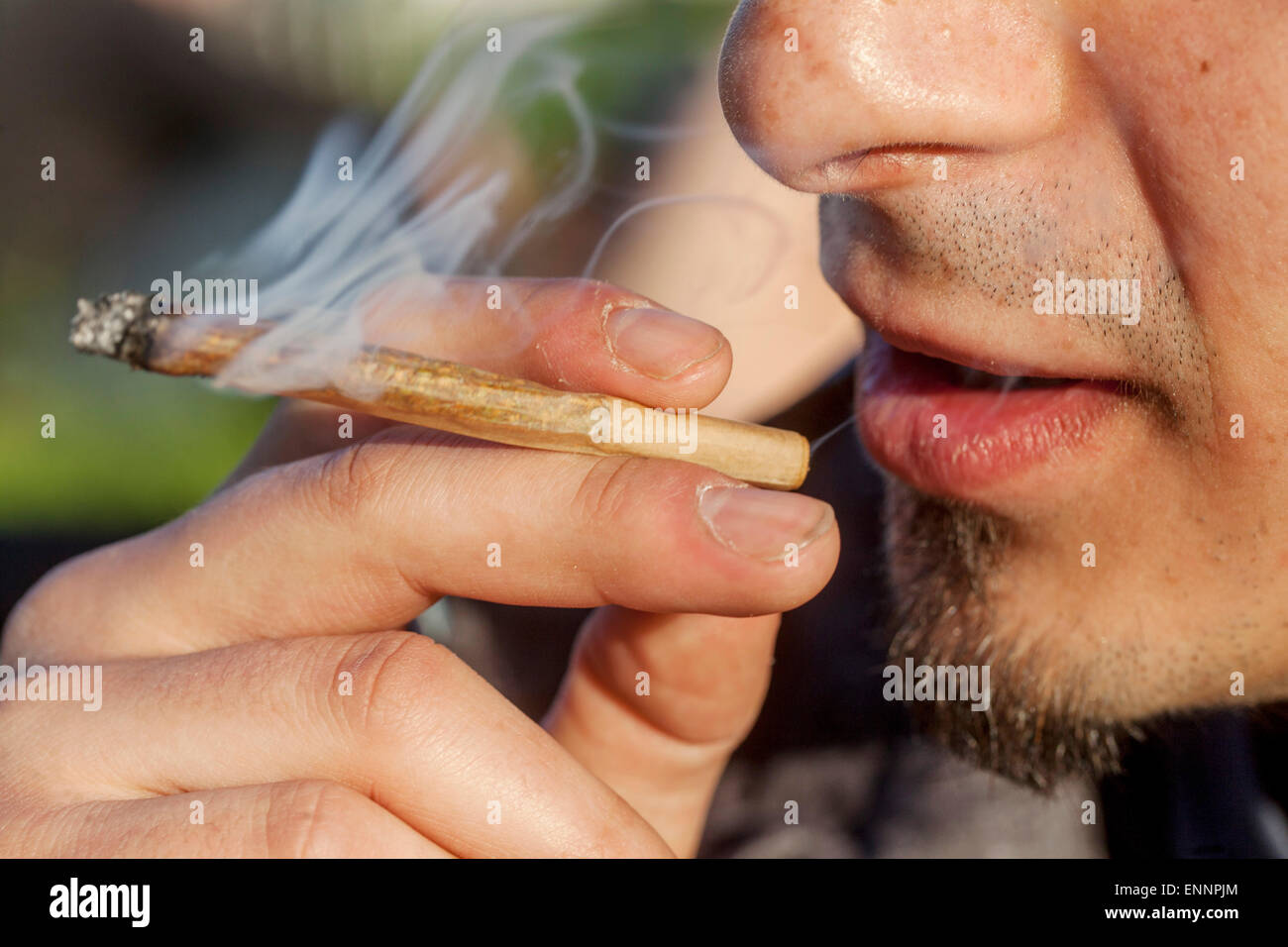 Close up, man smoking marijuana joint - Stock Image