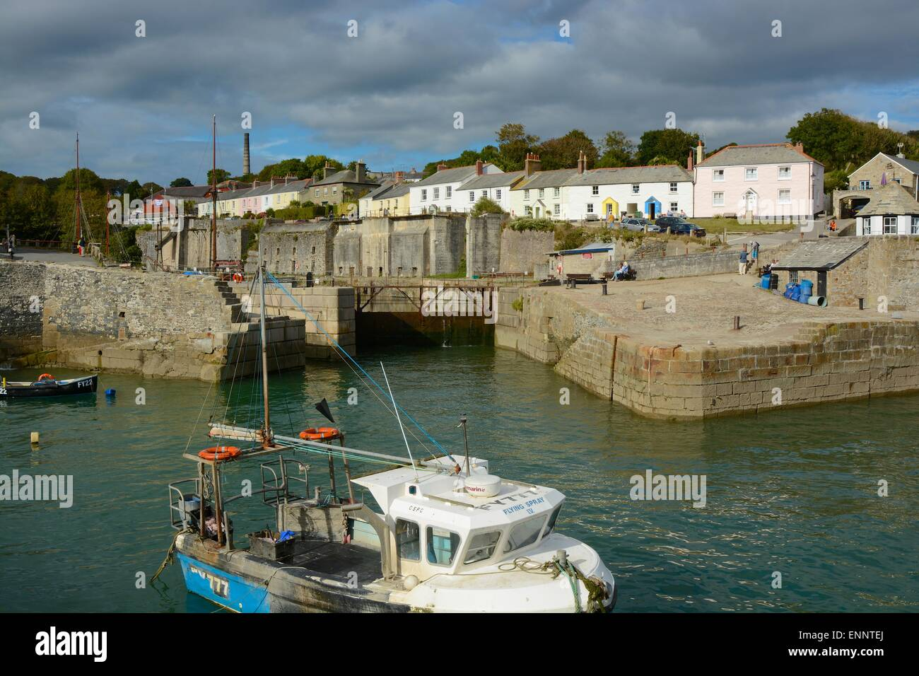 Charlestown Harbour entrance in Cornwall, England. With people walking and sitting and fishing boat in foreground - Stock Image