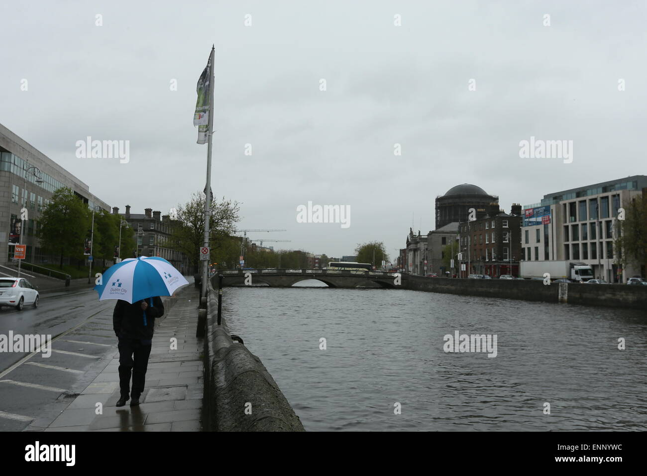 A man holding an umbrella walks along the Quays of the River Liffey. Image from Dublin city centre during a period - Stock Image
