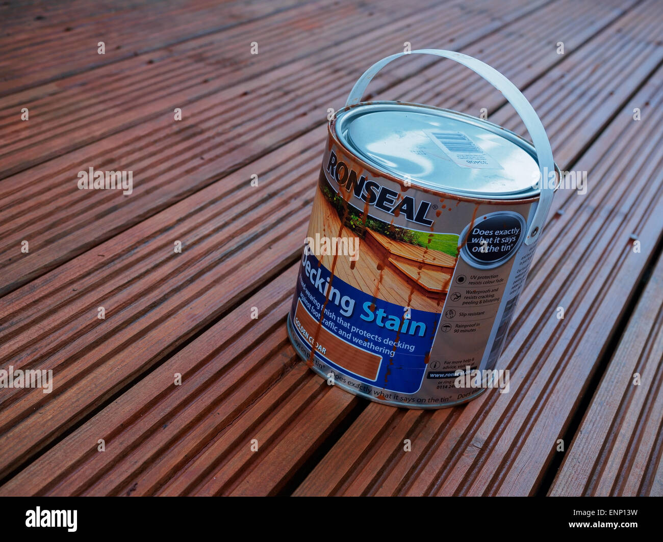 A freshly stained wooden deck, and a tin of stain paint. - Stock Image