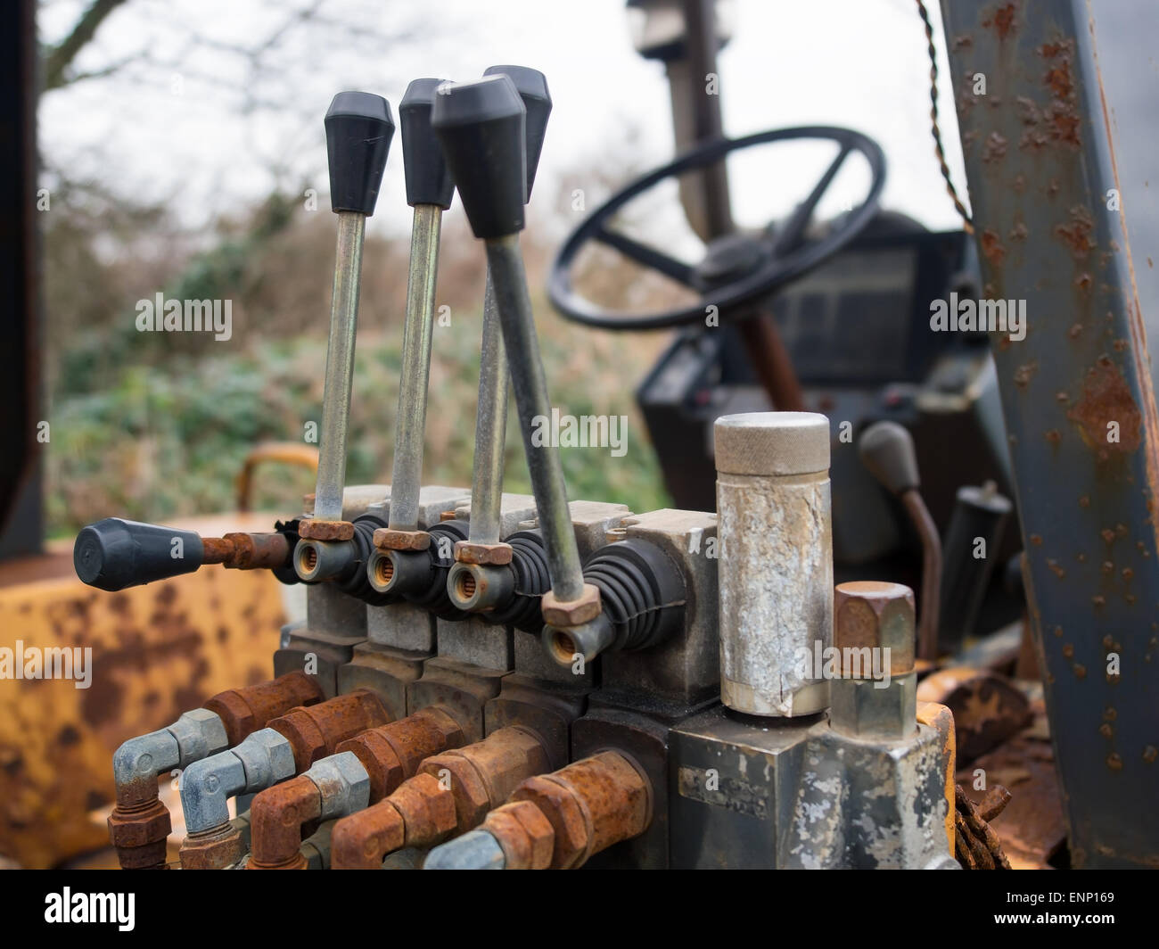 Rusty hydraulic valves and levers in the cab of an old tractor. - Stock Image