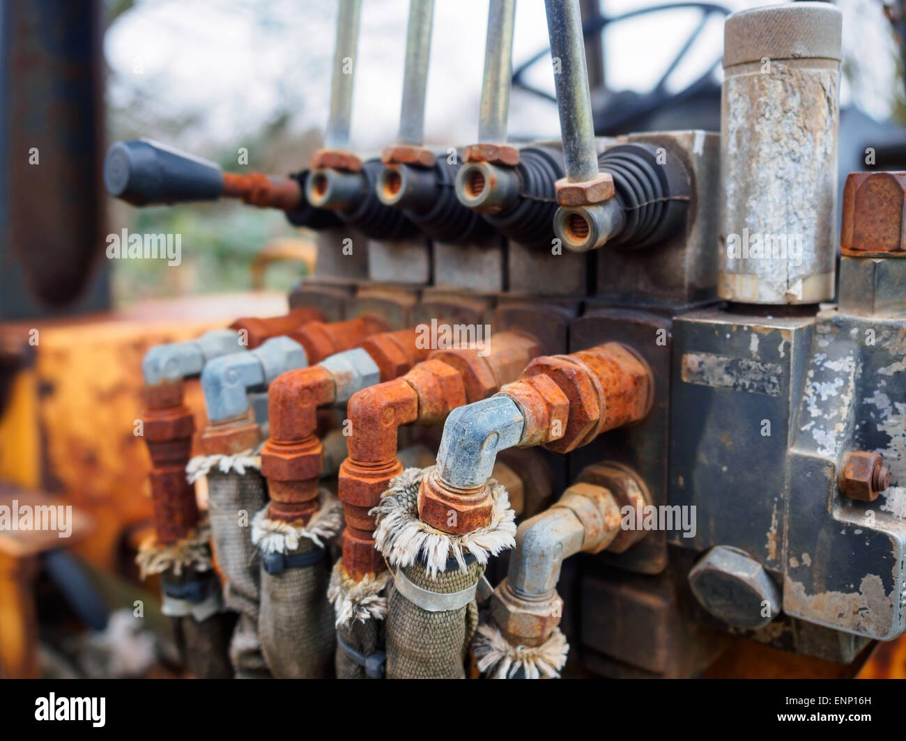 Rusty hydraulic valves and levers on an old tractor. - Stock Image