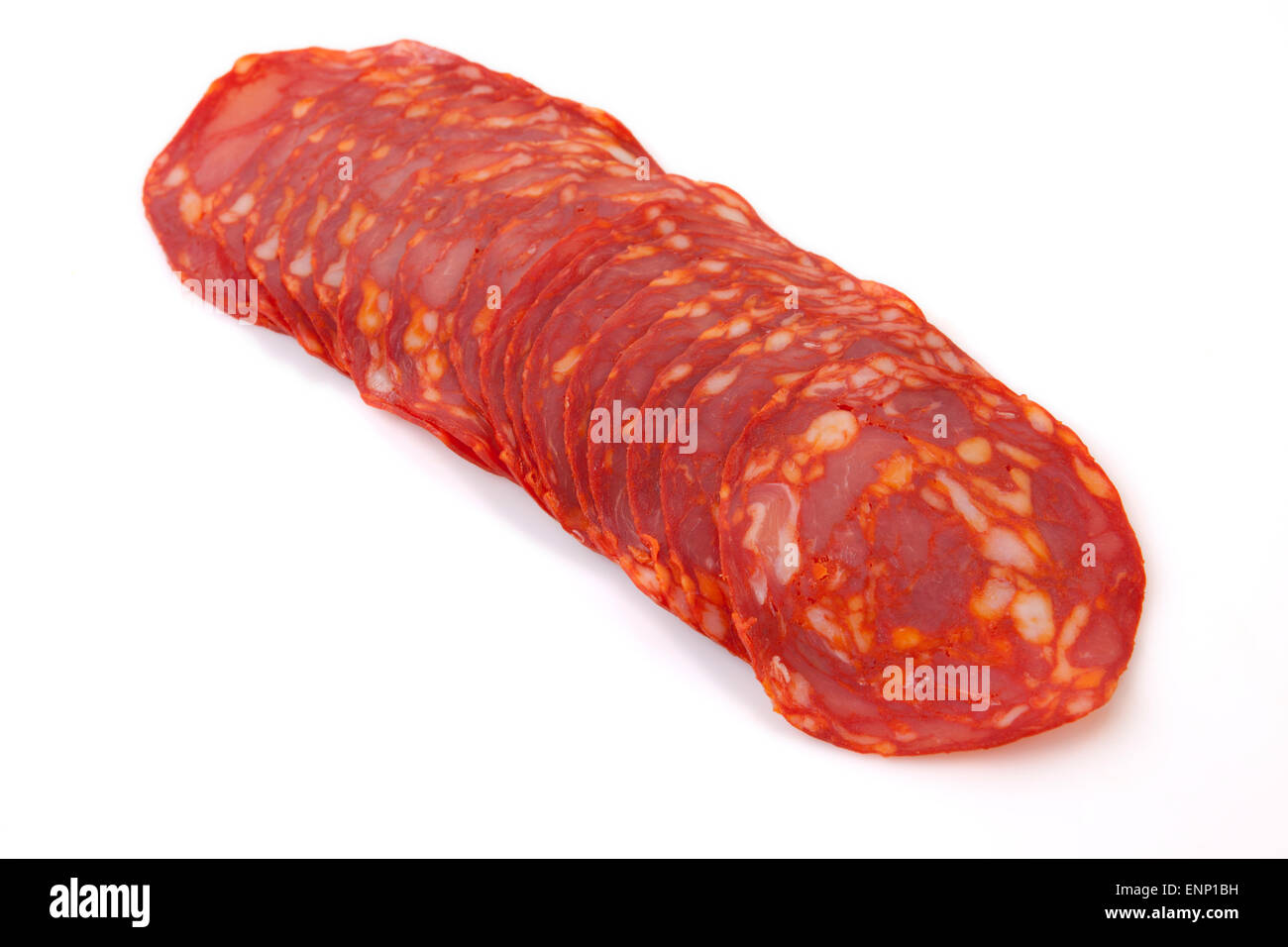 Some cut slices of red iberian chorizo. Isolated over white background - Stock Image