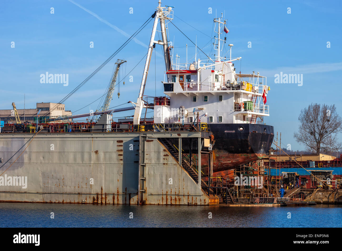 A view of a large ship under repair in dry dock at a shipyard. - Stock Image