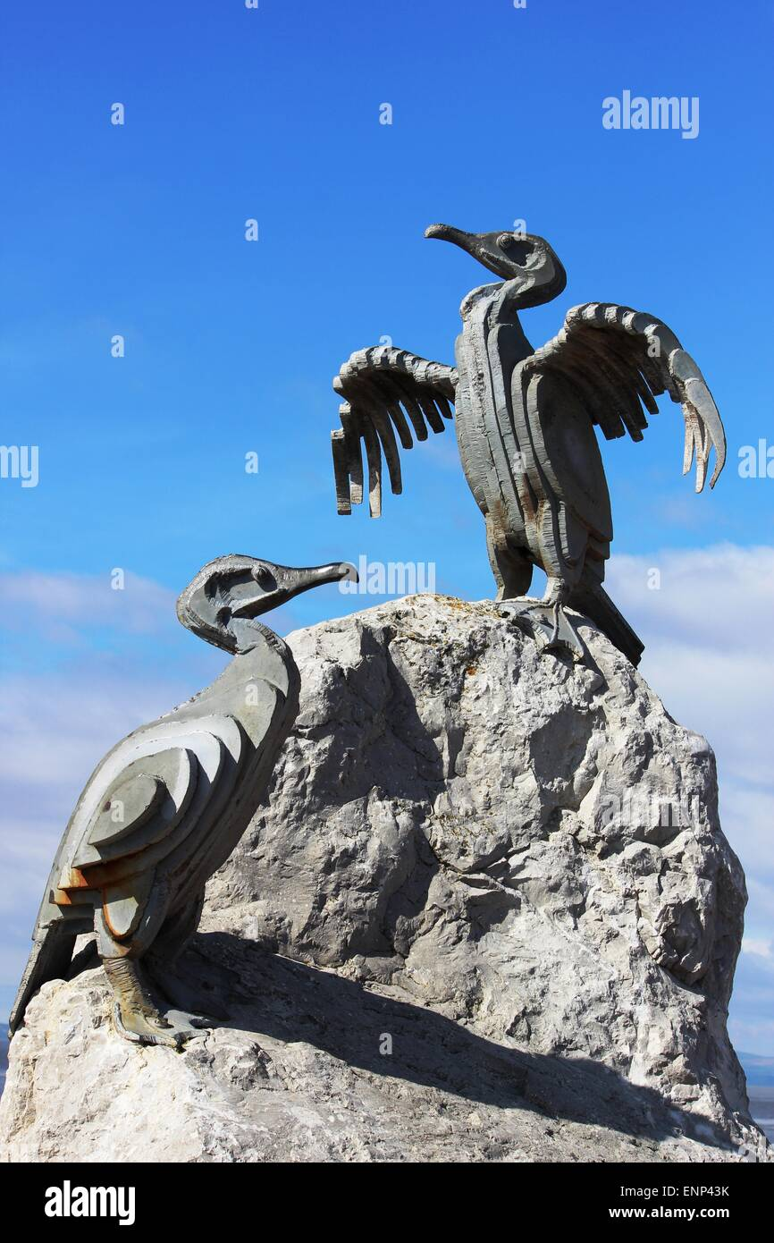 Stone sculptures of cormorants, part of the tern project, on rocks by the Stone Jetty, Morecambe, Lancashire, England. - Stock Image
