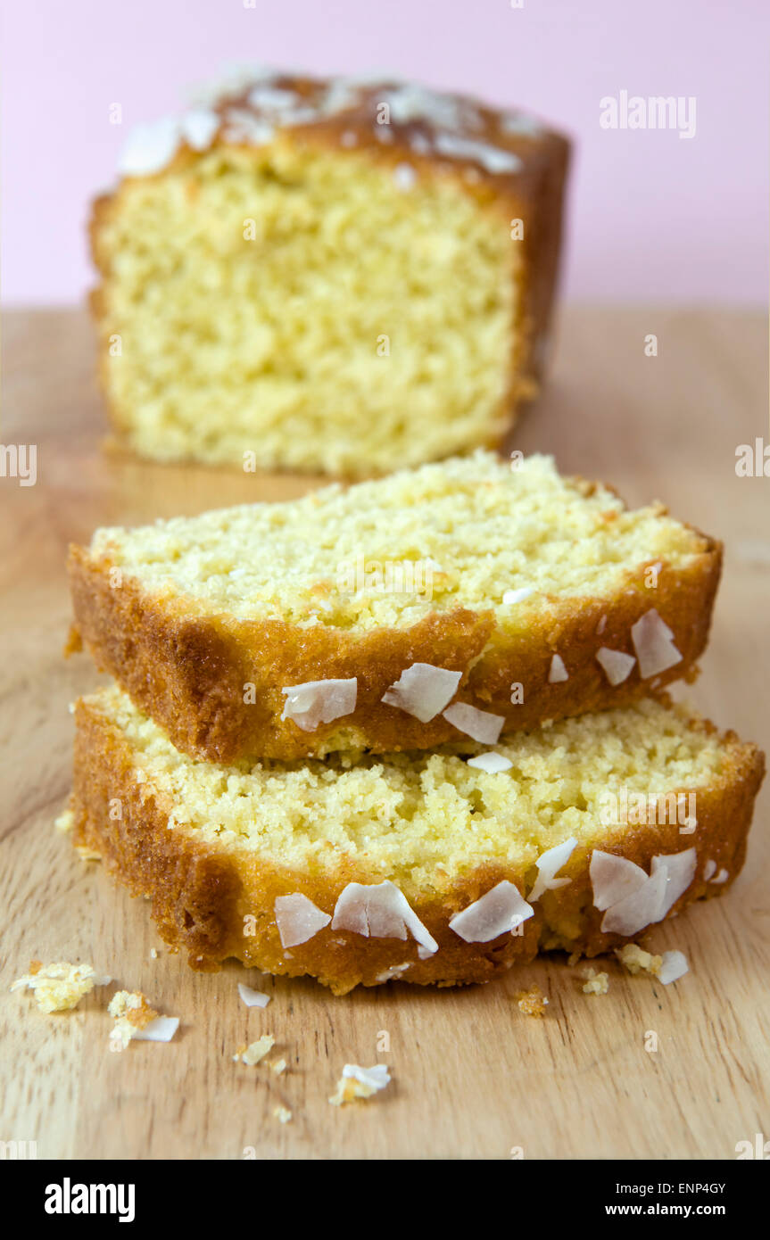 Sliced home made coconut cake on chopping board against a pink background - Stock Image
