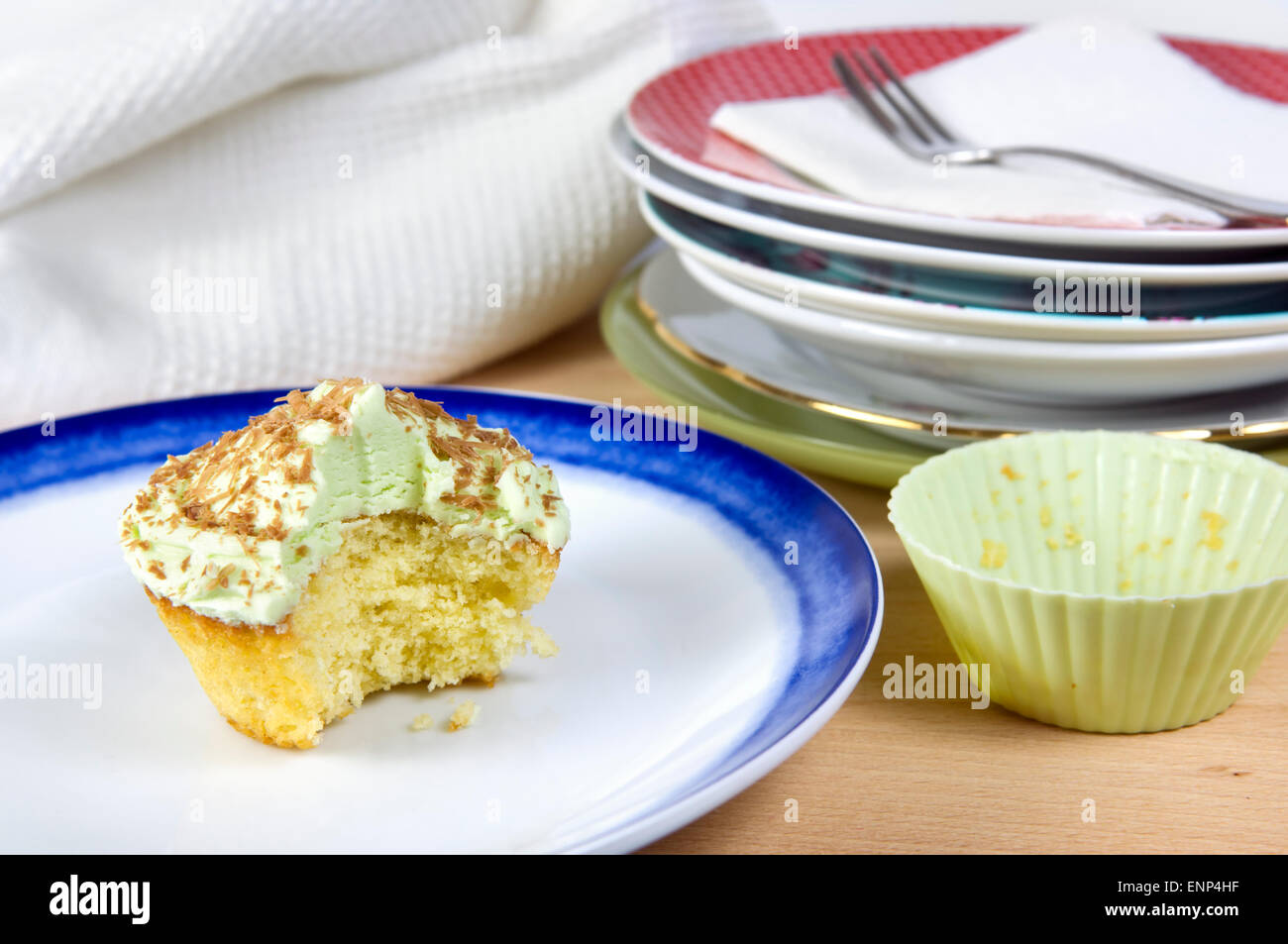 Pistachio cupcake with green icing, chocolate shavings and a bite taken out of, on a white and blue plate - Stock Image