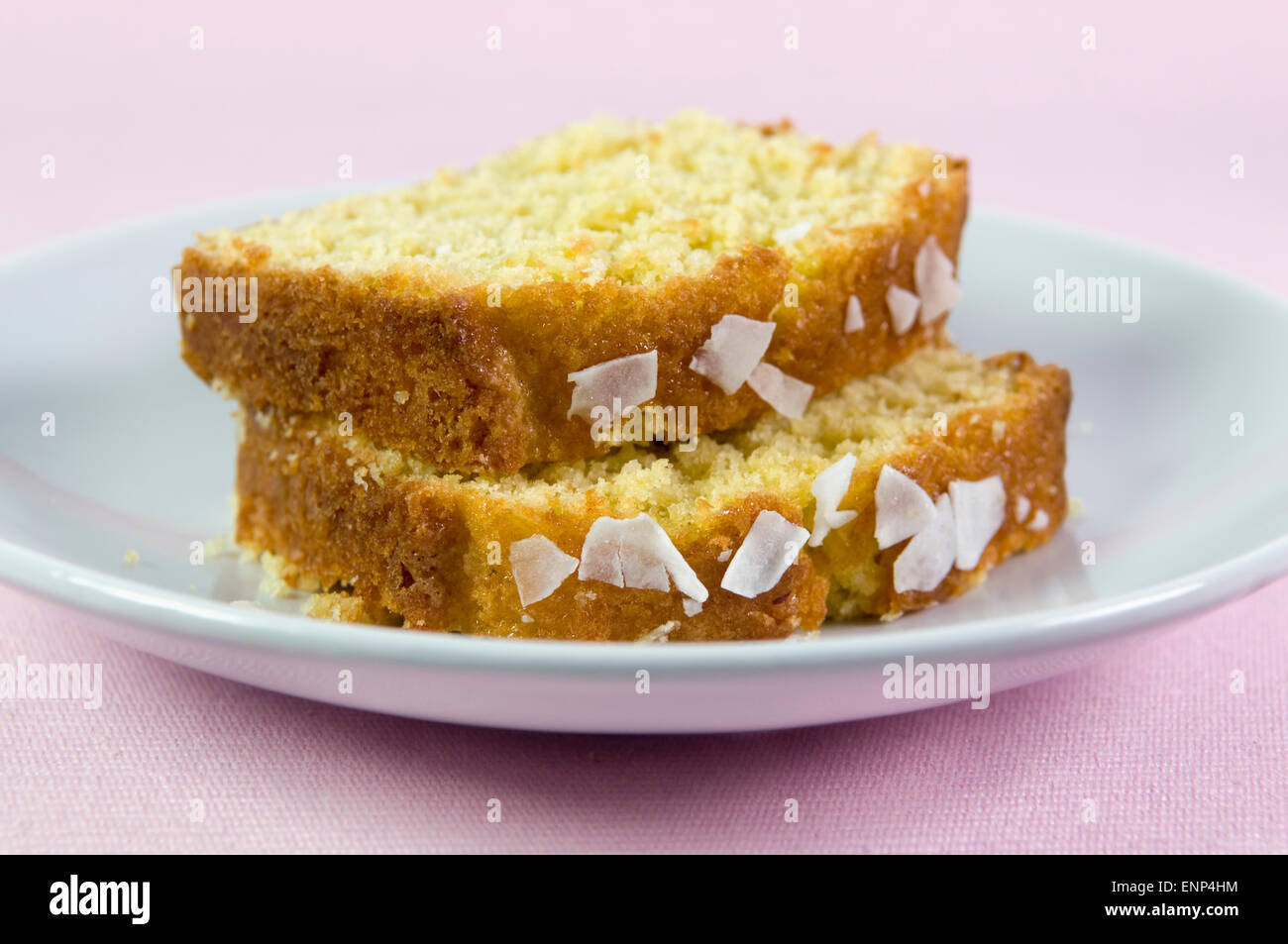 Sliced home made coconut cake on plate against a pink background - Stock Image