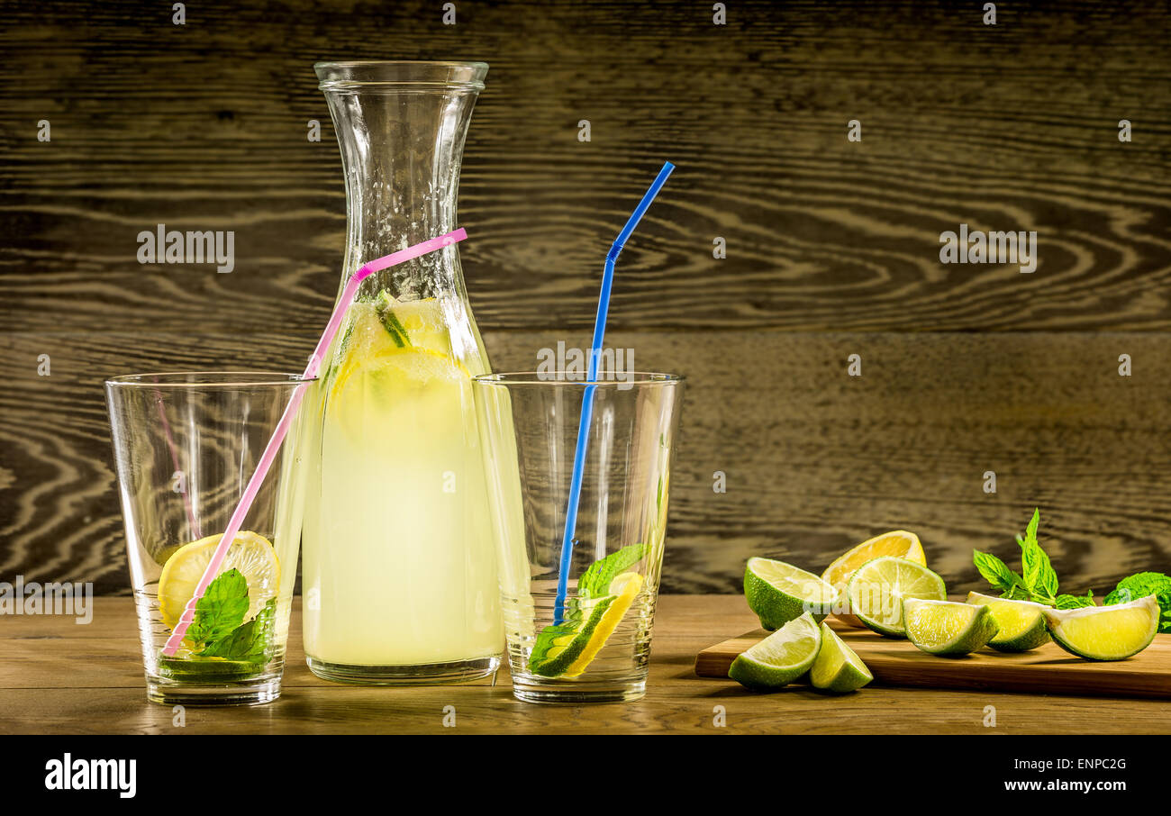 Refreshing lemonade drink and ripe fruits against wooden background Stock Photo