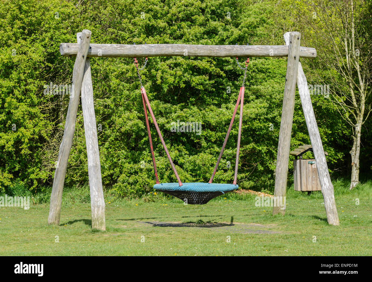 Modern swing with a wooden frame in a park. - Stock Image
