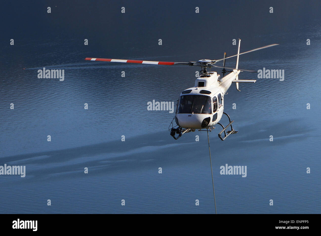 Helicopter used in freight transportation high in the mountains above a lake - Stock Image