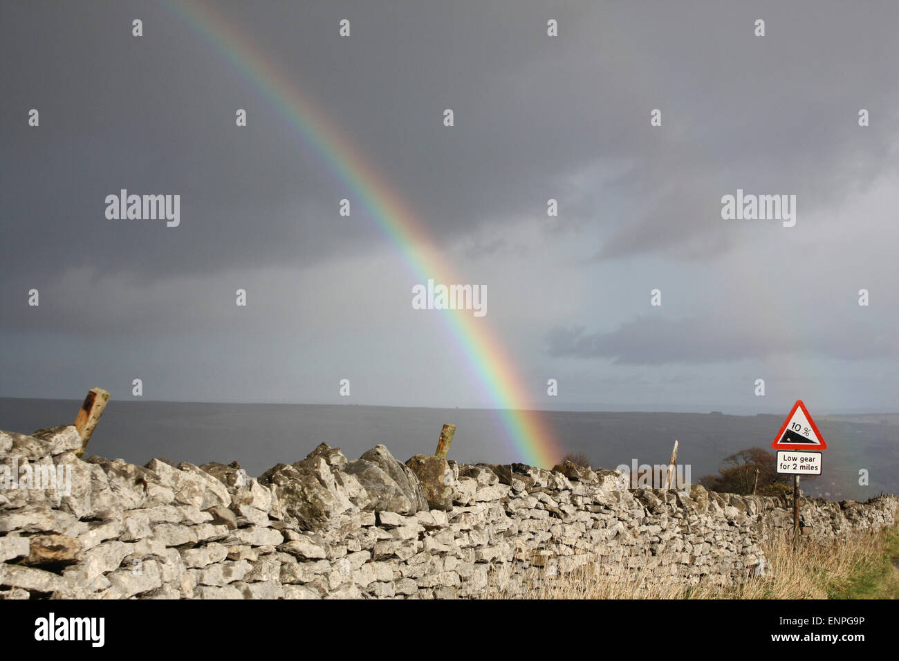 Rainbow behind a dry stone wall in Yorkshire. - Stock Image