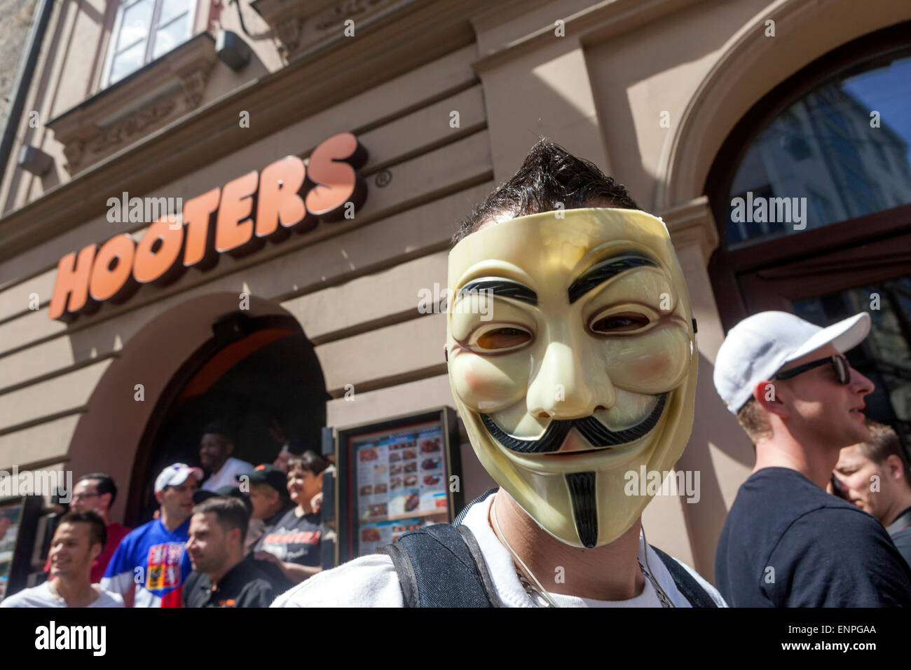 Man wearing Anonymous mask  in front of a bar Hooters, Prague Czech - Stock Image