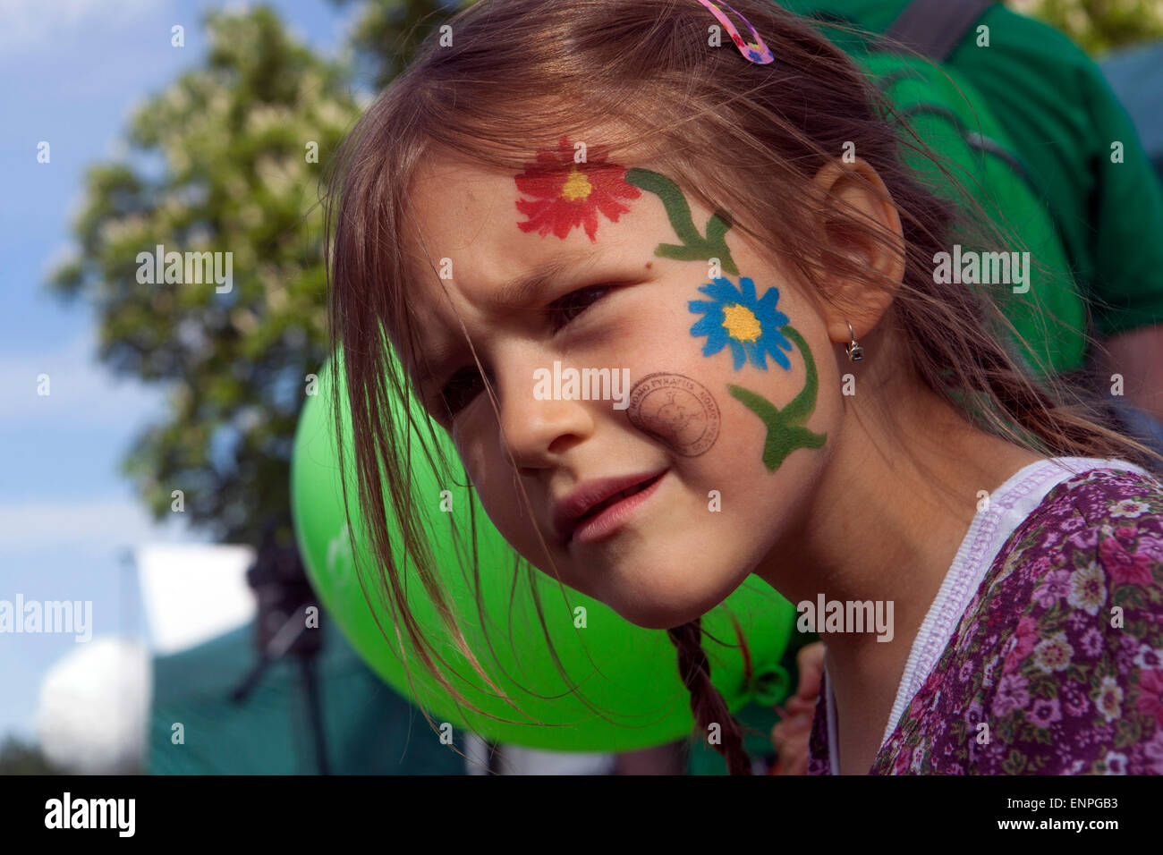 Girl with flowers painted on her cheek - Stock Image
