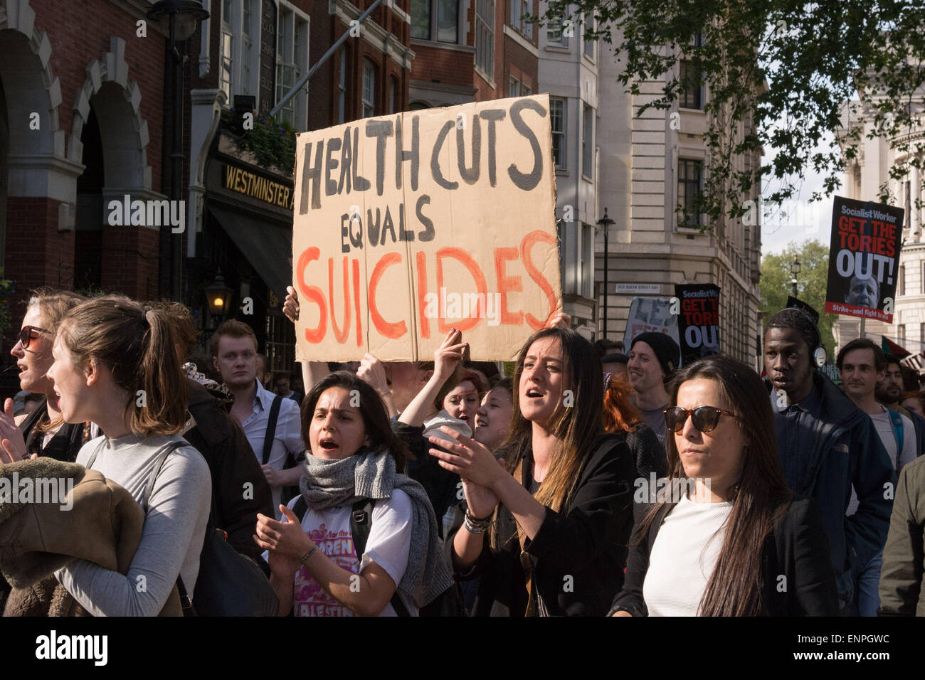 London, 9th May 2015. Protesters hold a placard which reads 'Health cuts equals suicides' as a demonstration - Stock Image