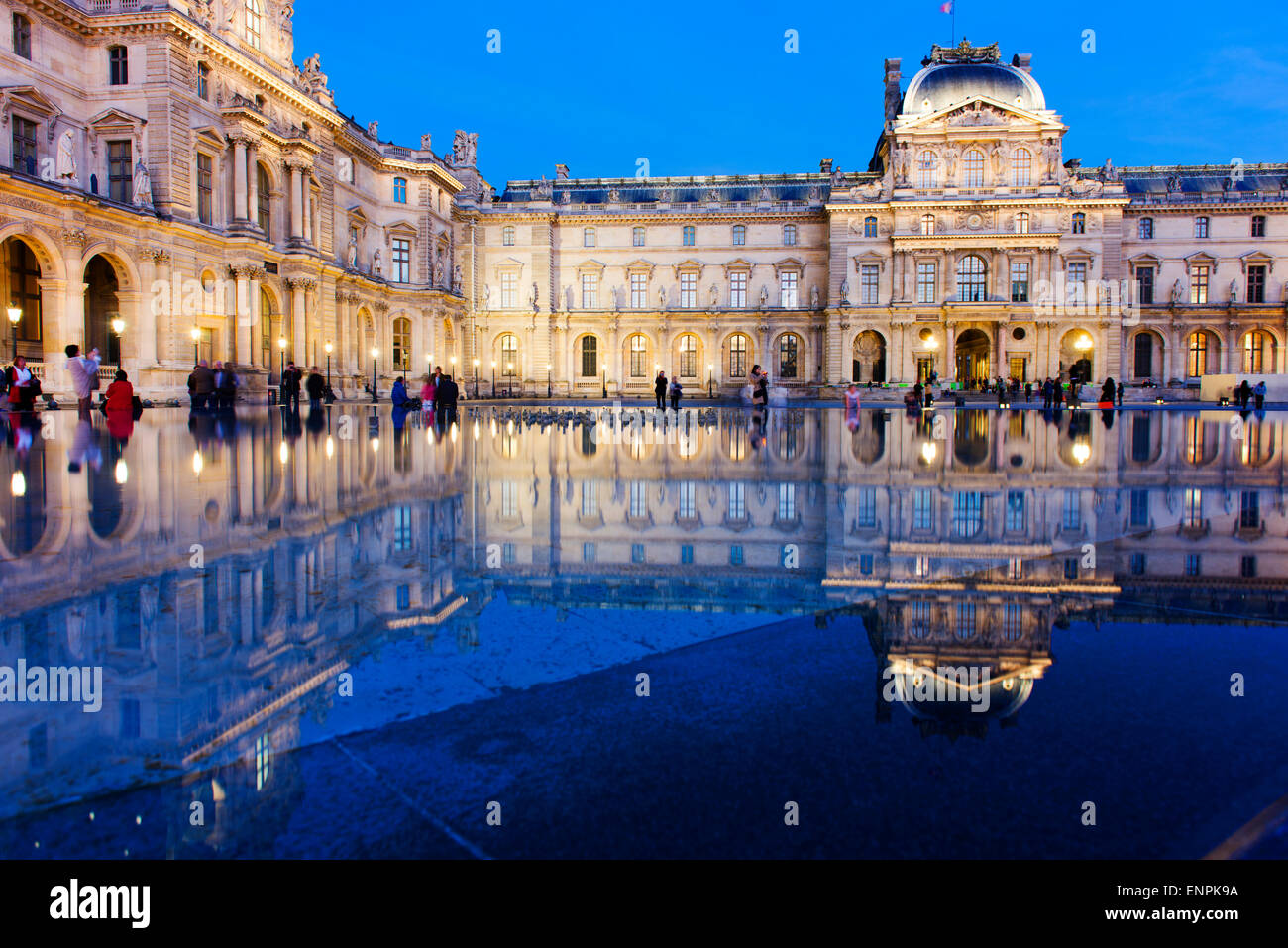 Louvre Museum at dusk, the blue hour, with reflections. - Stock Image