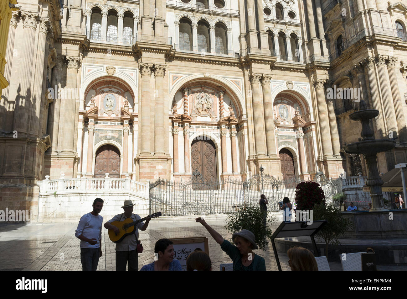 Malaga, Spain. Buskers and people sitting at a terrace by the Cathedral on Bishop Square. - Stock Image