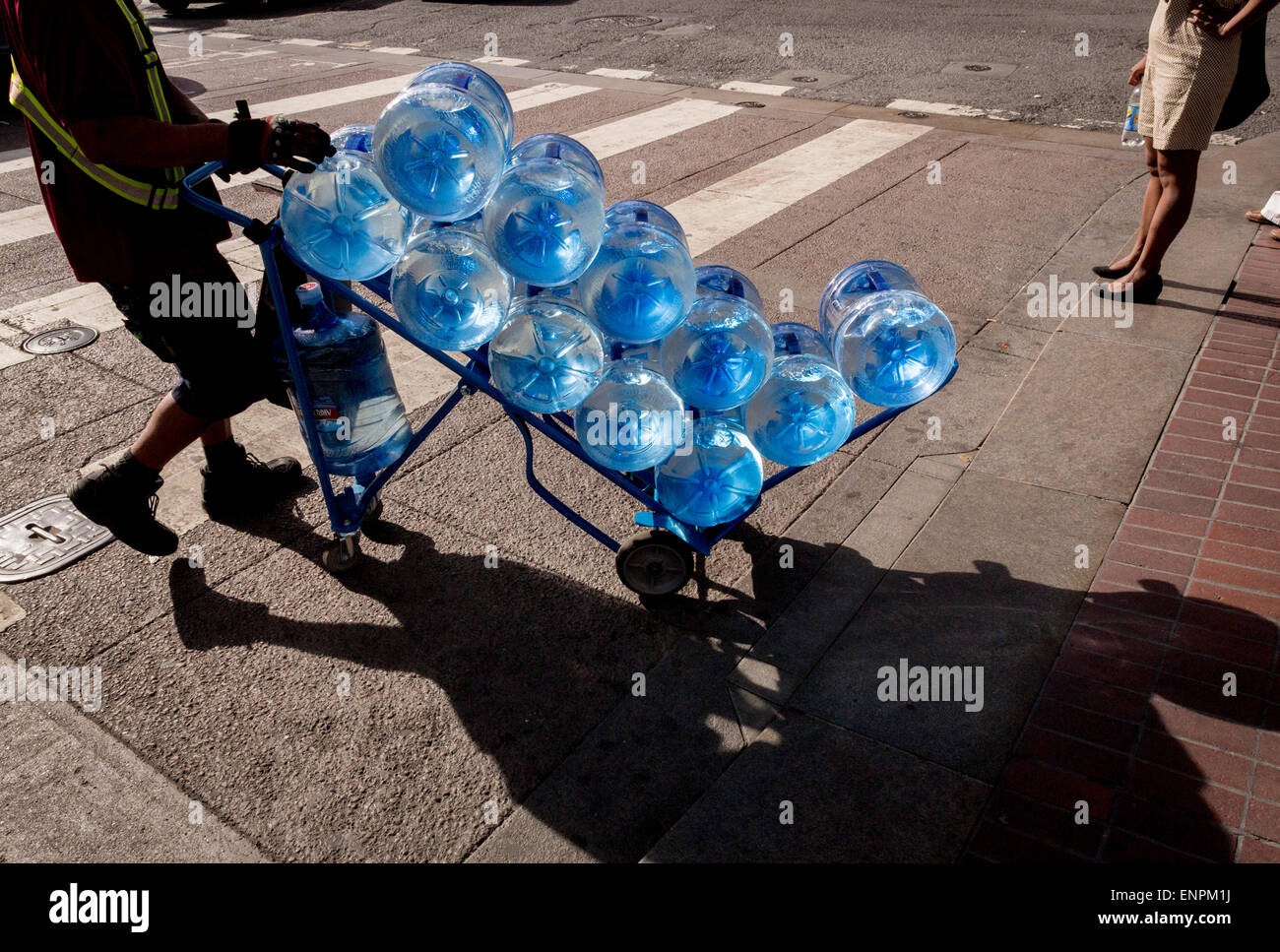 A delivery person wheels a cart of bottled water across a San Francisco street. - Stock Image