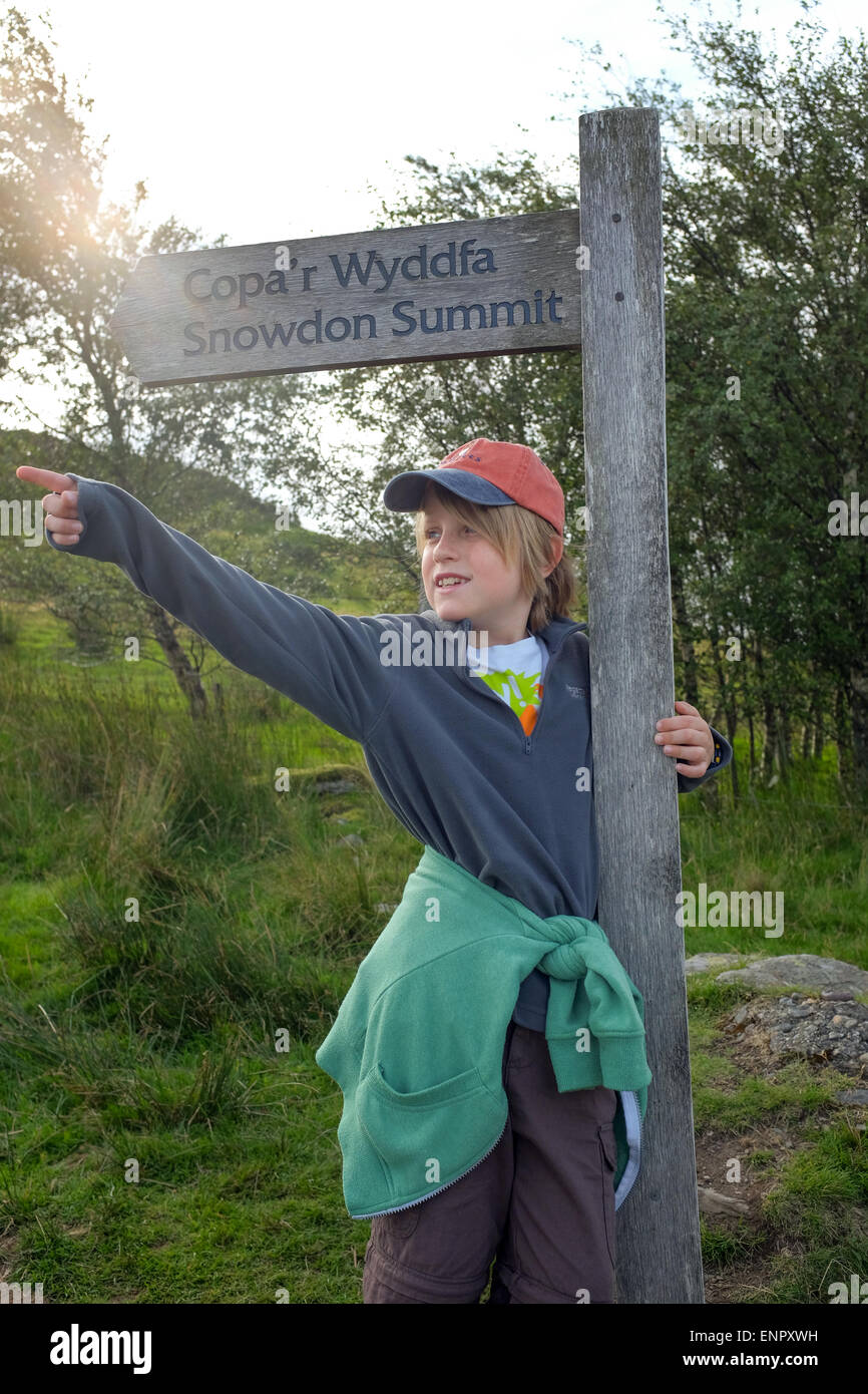 A boy prepares to climb up Mount Snowdon Snowdonia standing next to the path sign - Stock Image