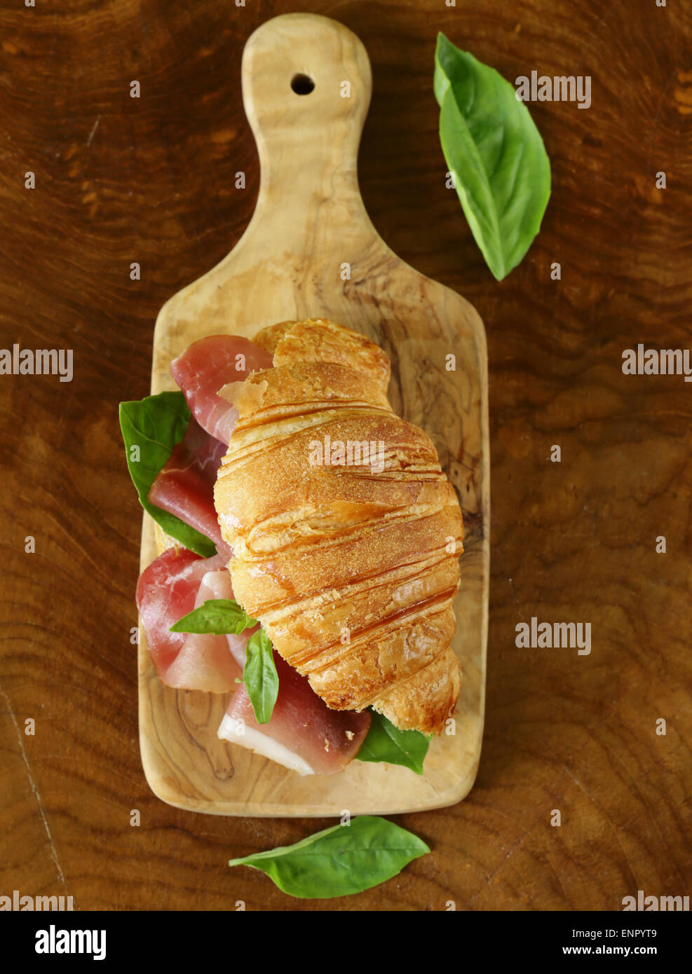 gourmet sandwich croissant with ham and basil - Stock Image