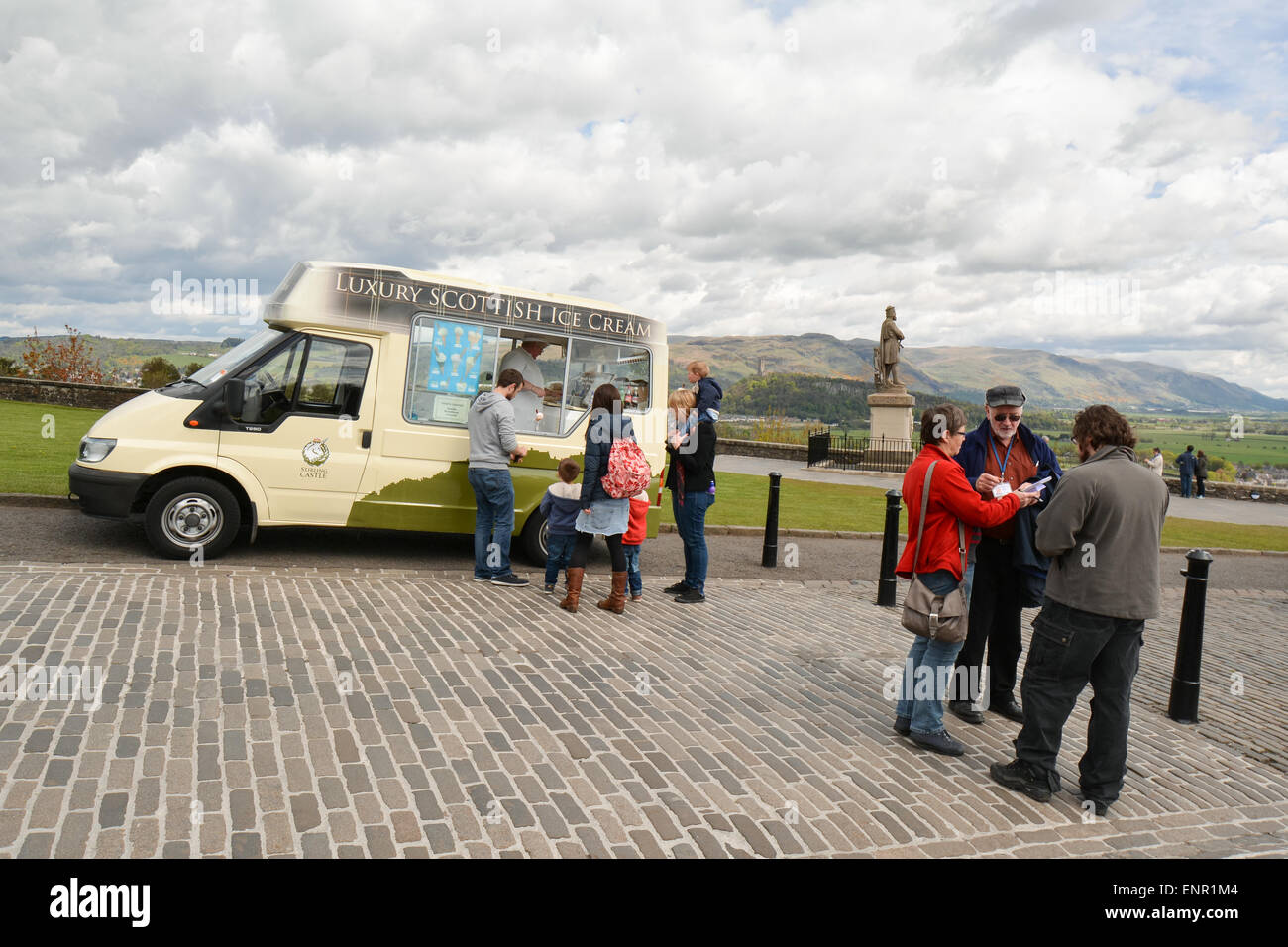 Ice cream van and tourists outside Stirling Castle with the Robert the Bruce statue and Wallace Monument behind Stock Photo
