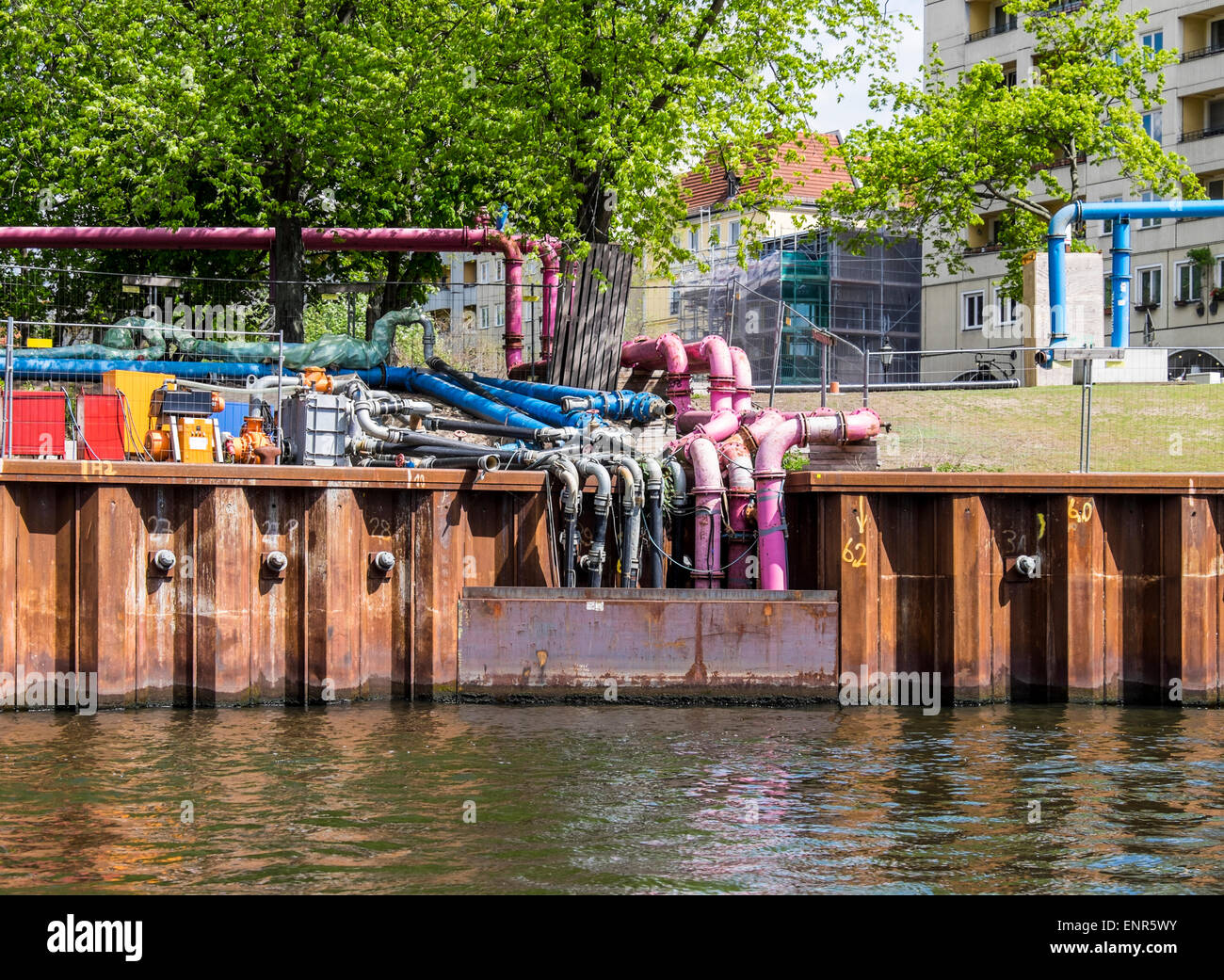 Colourful drainage pipes draining surface water into Spree River from building sites, Berlin - Stock Image