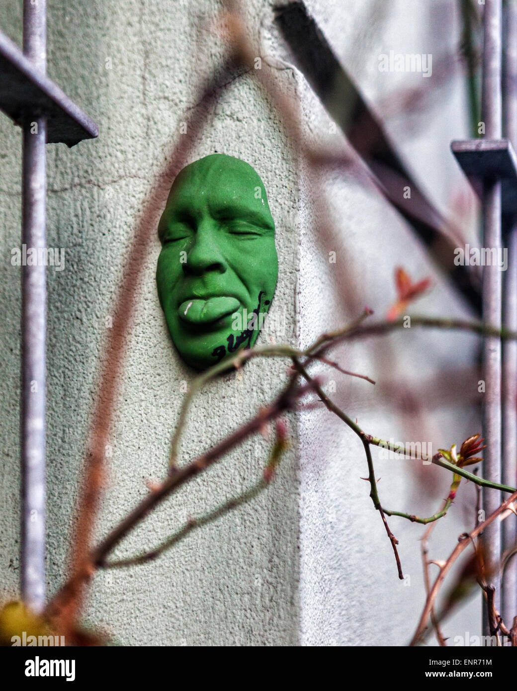 Urban street art - green 3-D self portrait, a face sculpture by Gregos on a city building, Berlin - Stock Image