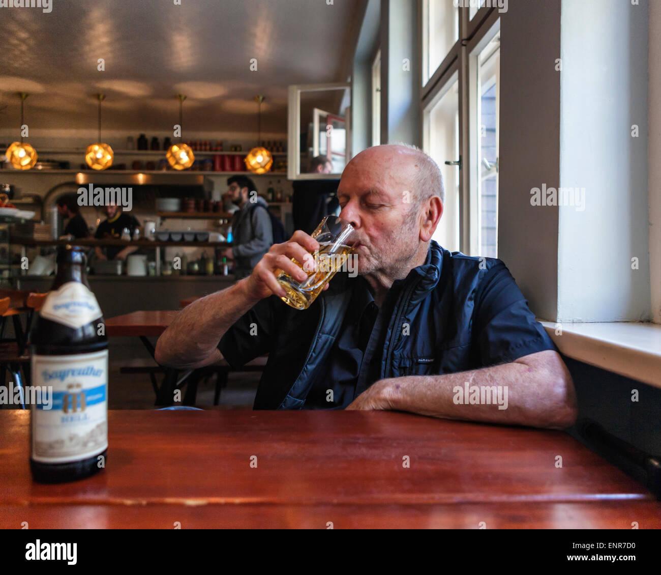 Mogg & Melzer diner interior and senior man drinking German Beer, Auguststrasse, Berlin - Stock Image