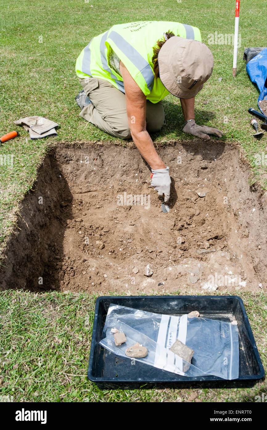 England, Margate. Archaeologist excavating Roman period trench with a trowel during a dig. Sunshine, daylight. - Stock Image