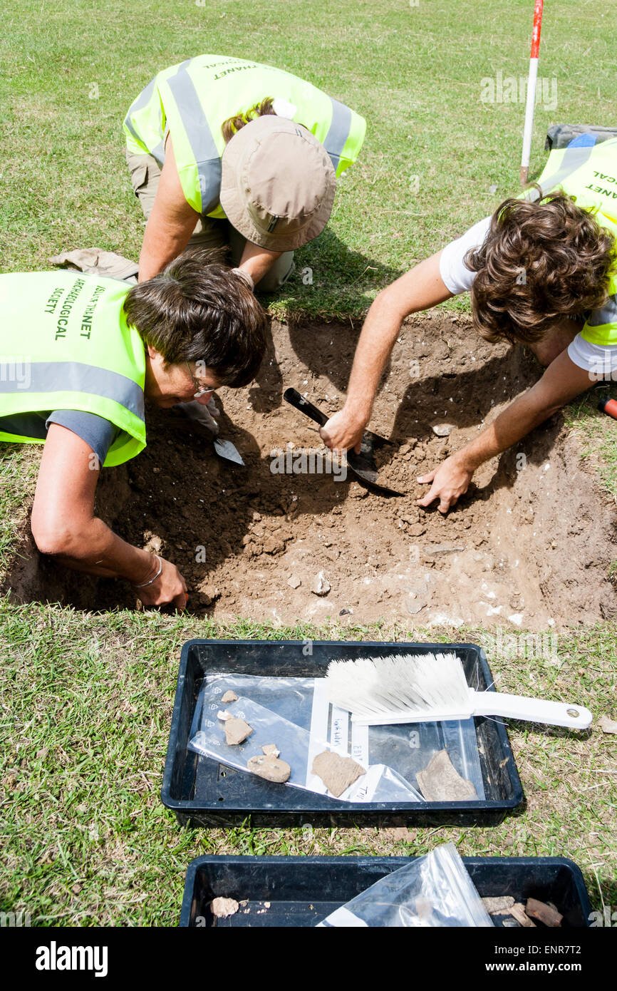 England, Margate. Three archaeologists excavating Roman period trench with trowels during a dig. Sunshine, daylight. - Stock Image