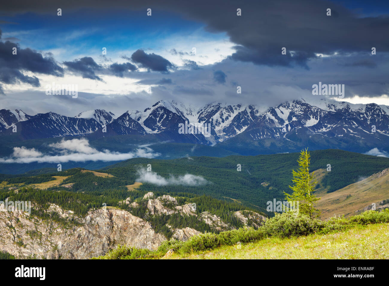 Landscape with snowy mountains and cloudy sky - Stock Image