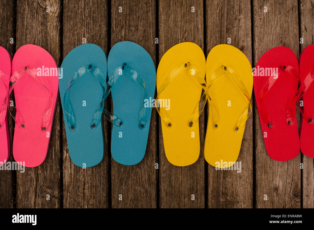 Multicolored flip flops on wooden deck - Stock Image