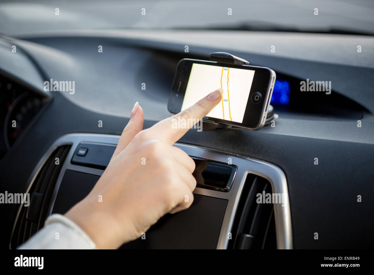 Female driver using touchscreen smartphone with GPS navigation Stock Photo