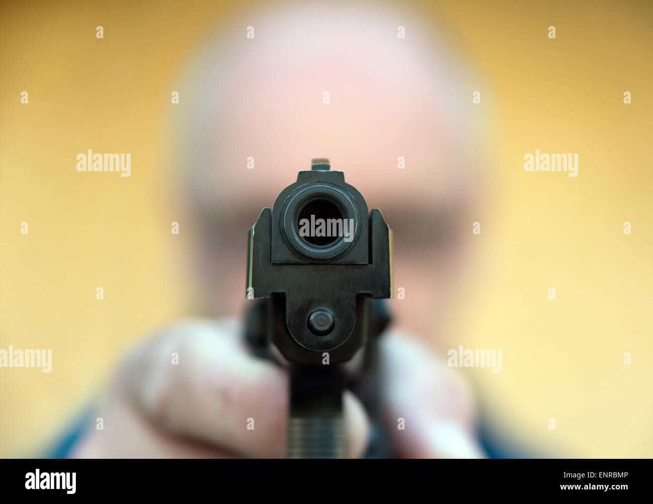 Anonymous man aiming gun at the viewer - Stock Image